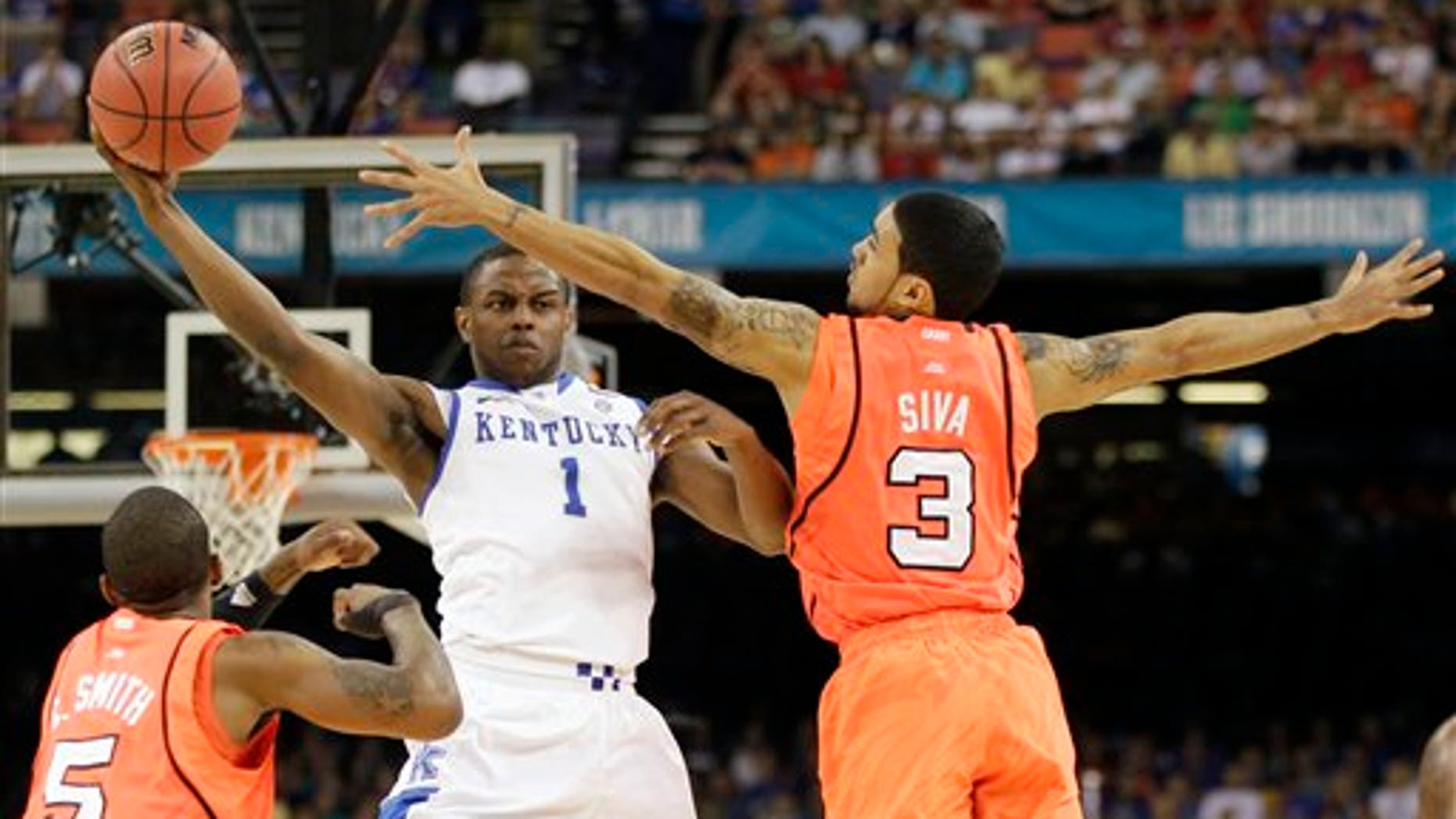 March 31, 2012: Kentucky's Darius Miller (1) passes over Louisville's Chris Smith (5) and Peyton Siva (3) during the first half of an NCAA Final Four semifinal college basketball tournament game in New Orleans.