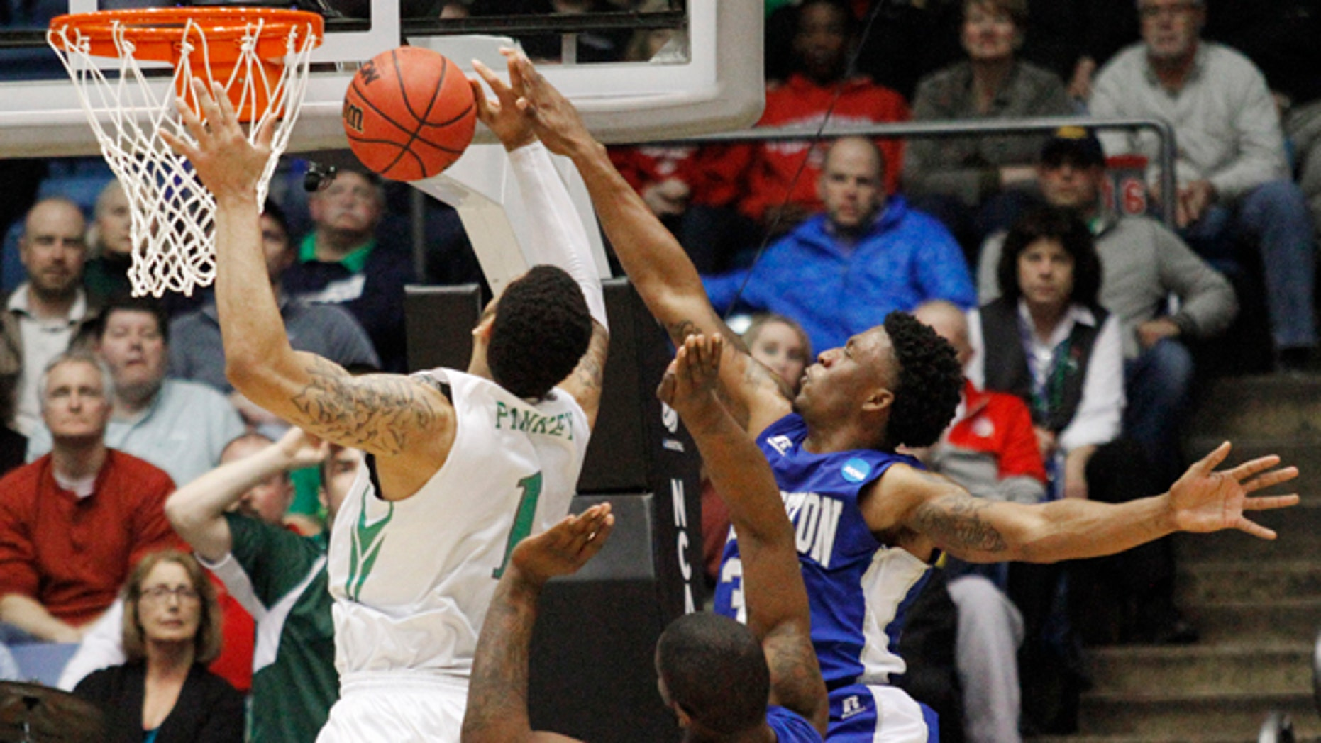 March 17, 2015: Hampton's Reginald Johnson, right, blocks a shot by Manhattan's Ashton Pankey (1) in the second half of a first round NCAA tournament basketball game Tuesday, March 17, 2015 in Dayton, Ohio. (AP Photo/Skip Peterson)