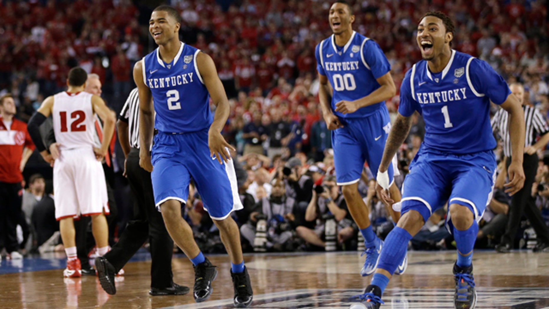 April 5, 2014: Kentucky's Aaron Harrison (2), Marcus Lee (00) and James Young, right, celebrate at the end of their 74-73 victory over Wisconsin in an NCAA Final Four tournament college basketball semifinal game in Arlington, Texas. (AP Photo/David J. Phillip)