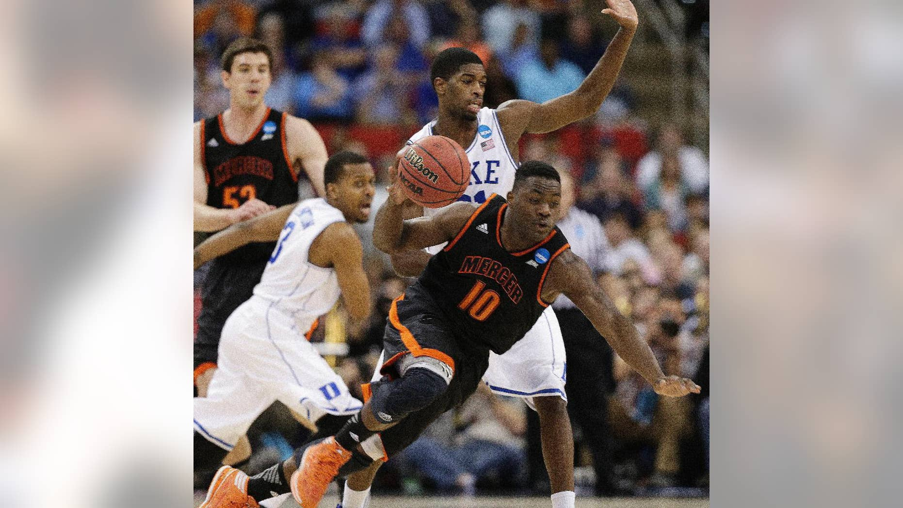 Mercer guard Ike Nwamu (10) moves the ball against Duke forward Amile Jefferson (21) during the second half of an NCAA college basketball second-round game, Friday, March 21, 2014, in Raleigh, N.C. (AP Photo/Chuck Burton)