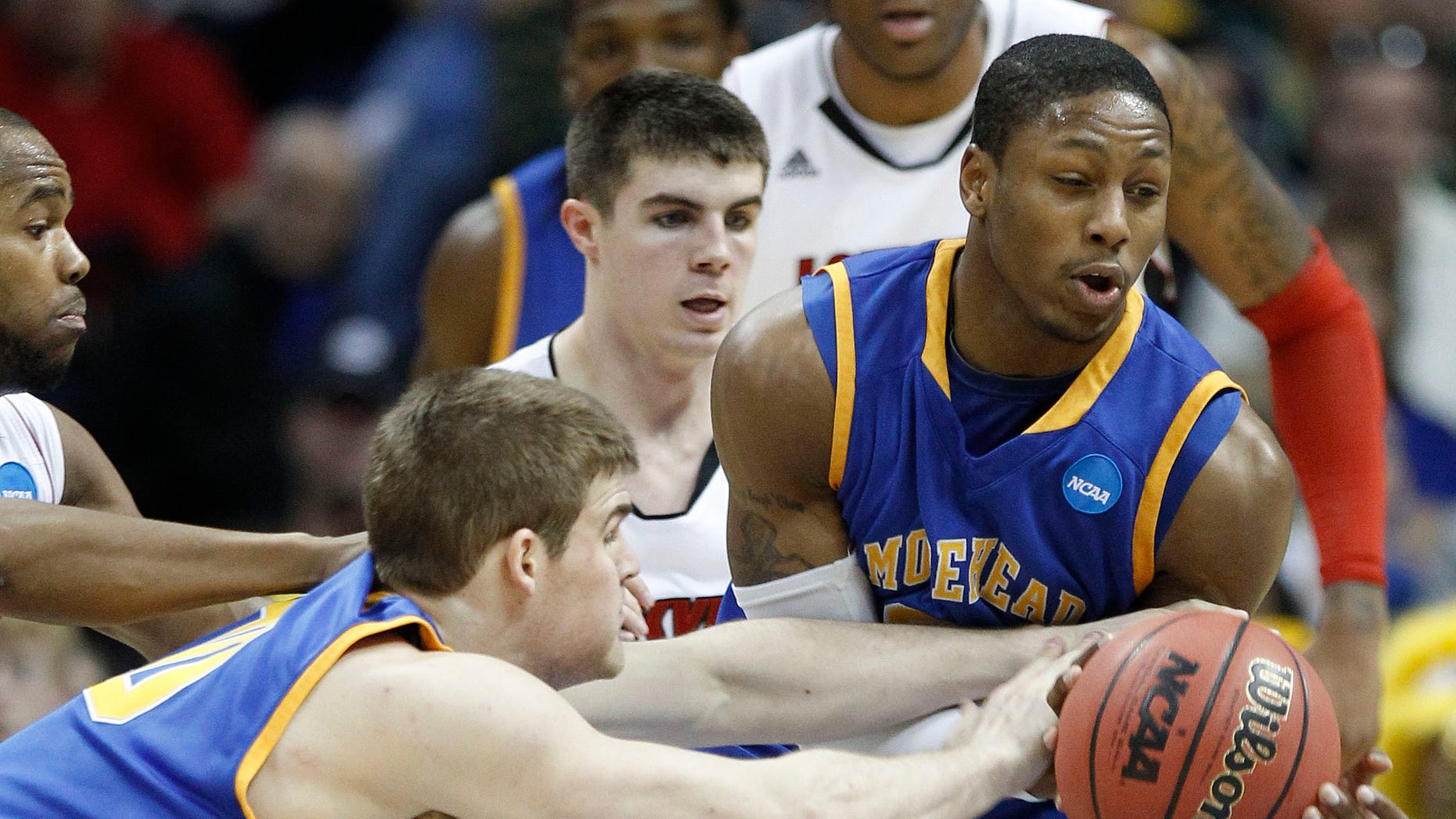 March 17: Morehead State forward Drew Kelly (0) and guard Demonte Harper (22) reach for a loose ball in the second half against Louisville during a Southwest regional second round NCAA tournament college basketball game in Denver. (AP)