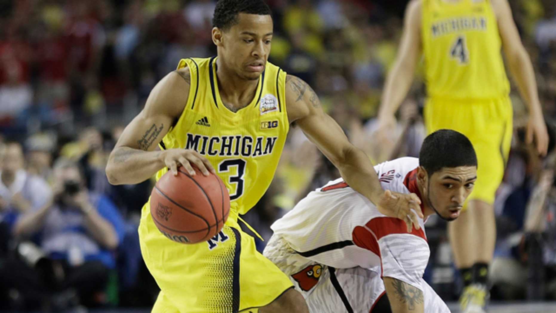 April 8, 2013: Louisville guard Peyton Siva (3) and Michigan guard Trey Burke (3) work during the second half of the NCAA Final Four tournament college basketball championship game.