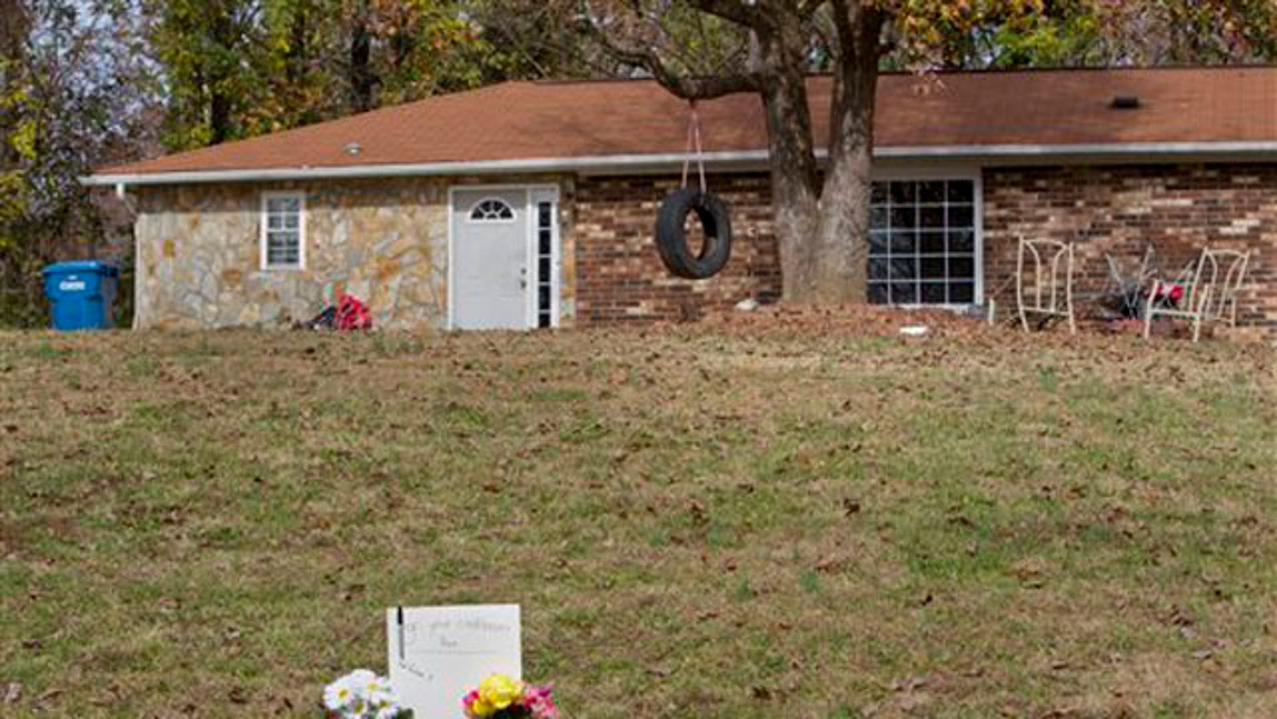 A memorial stands in front of a house on Cocoa Drive, where Mary Ann Holder is believed to have shot one of her sons, his girlfriend, and a niece and nephew, near Greensboro, N.C., Monday, Nov. 21, 2011.