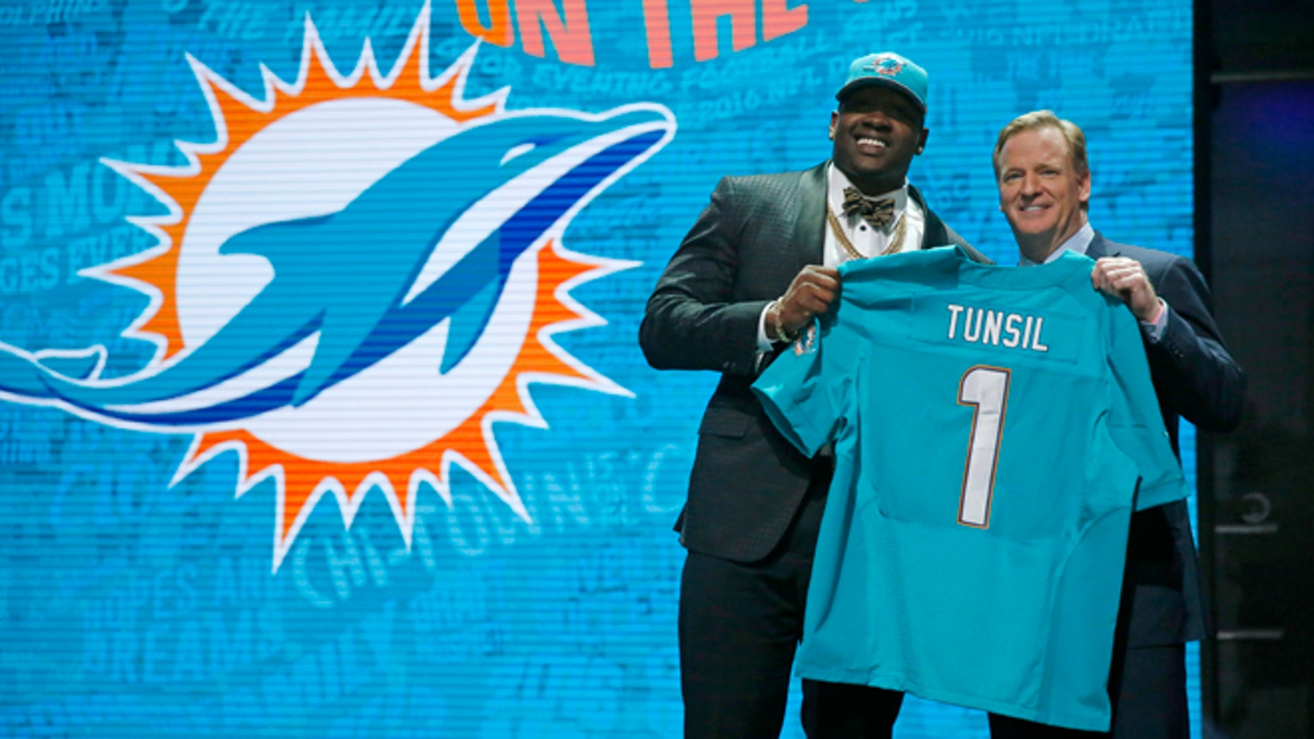 Mississippis Laremy Tunsil poses for photos with NFL commissioner Roger Goodell after being selected by the Miami Dolphins as the 13th pick in the first round of the 2016 NFL football draft, Thursday, April 28, 2016, in Chicago. (AP Photo/Charles Rex Arbogast)