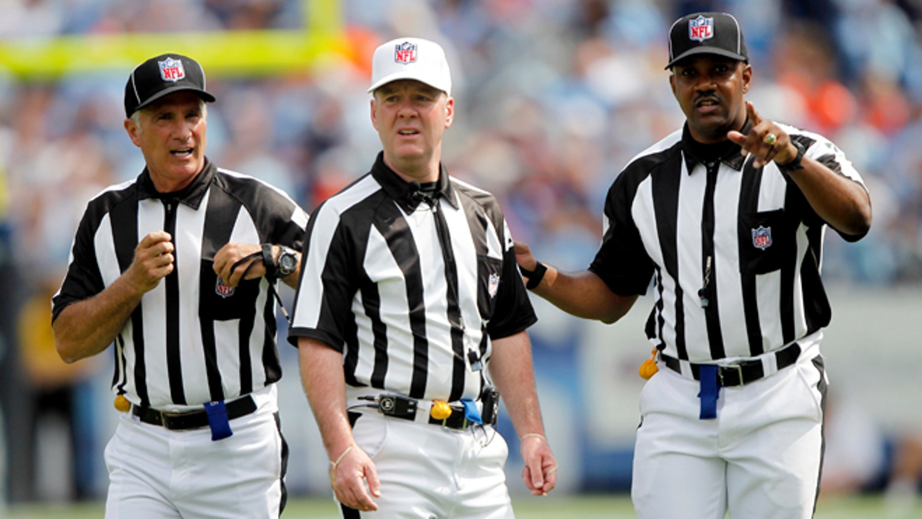 FILE - In this Sept. 25, 2011, file photo, officials confer in the third quarter of an NFL football game between the Denver Broncos and the Tennessee Titans in Nashville, Tenn. The NFL and referees' union reached a tentative agreement on Wednesday, Sept. 26, 2012, to end a three-month lockout that triggered a wave of frustration and anger over replacement officials and threatened to disrupt the rest of the season. (AP Photo/Wade Payne, File)