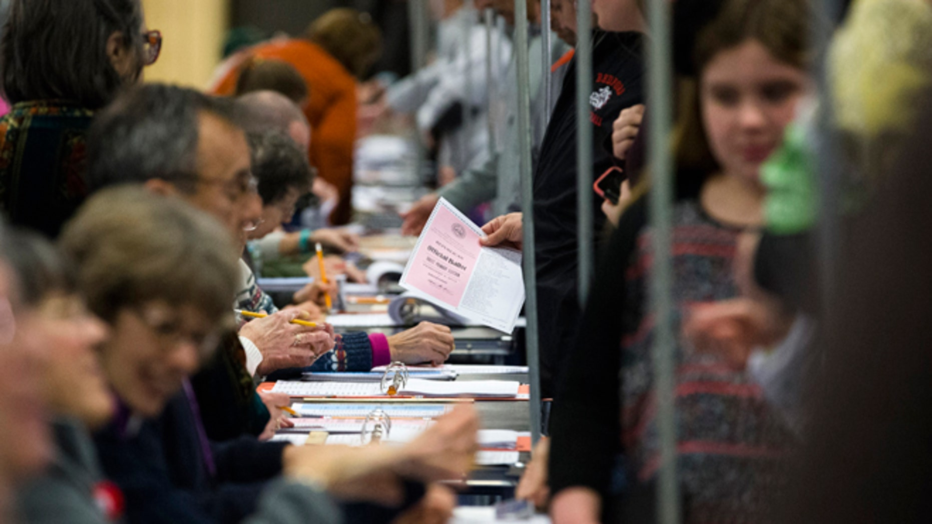 Voters collect their ballots at a polling place inside Bedford High School, Tuesday, Feb. 9, 2016, in Bedford, N.H. (AP Photo/John Minchillo)