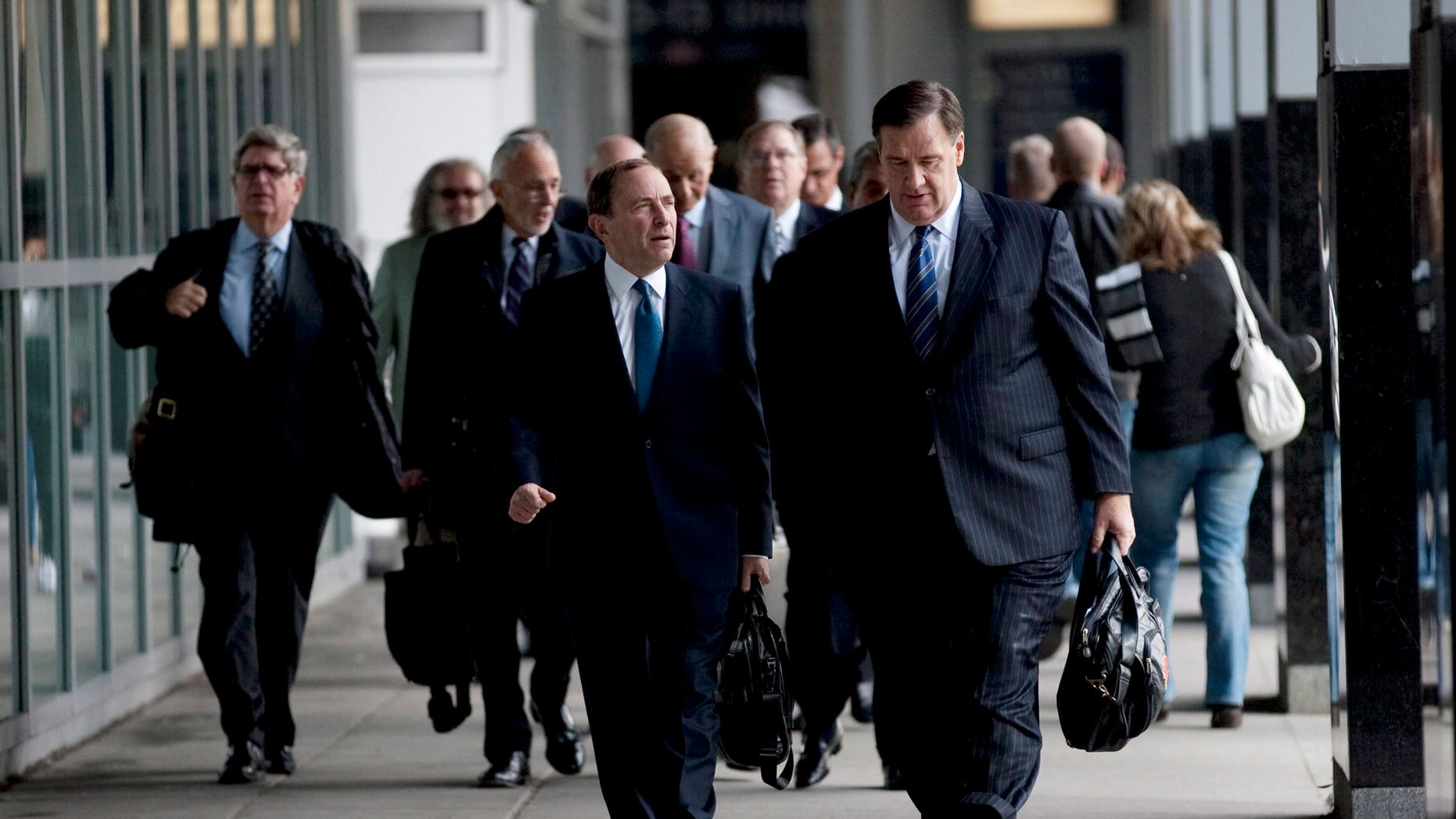 Oct. 18, 2012 File of NHL Commissioner Gary Bettman, left foreground, and Calgary Flames co-owner Murray Edwards arrive for negotiations with the Players Association in Toronto.