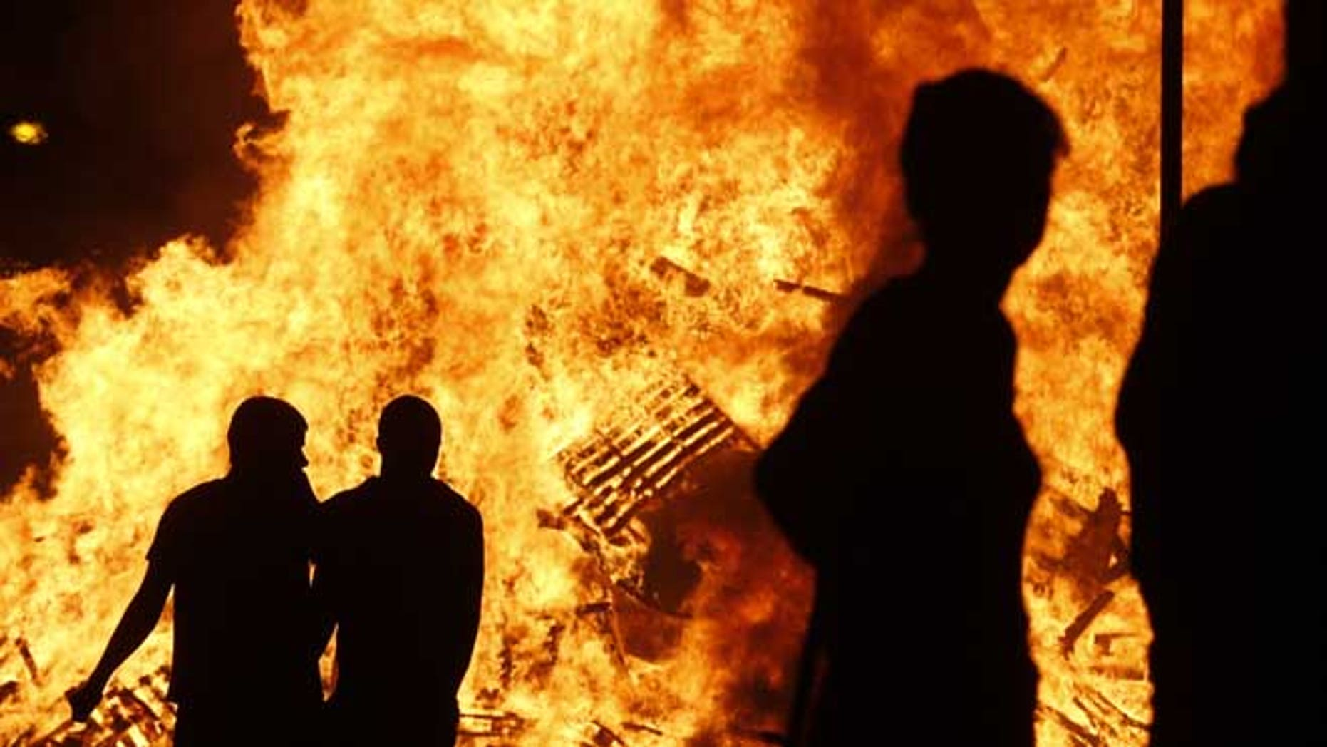 July 11, 2013: Loyalists watch a bonfire in the Sandy Row area of Belfast, Northern Ireland. Hundreds of fires were set alight Thursday as loyalists celebrate the July 12, remembering the defeat of the Catholic King James, by the Protestant William of Orange in 1690.