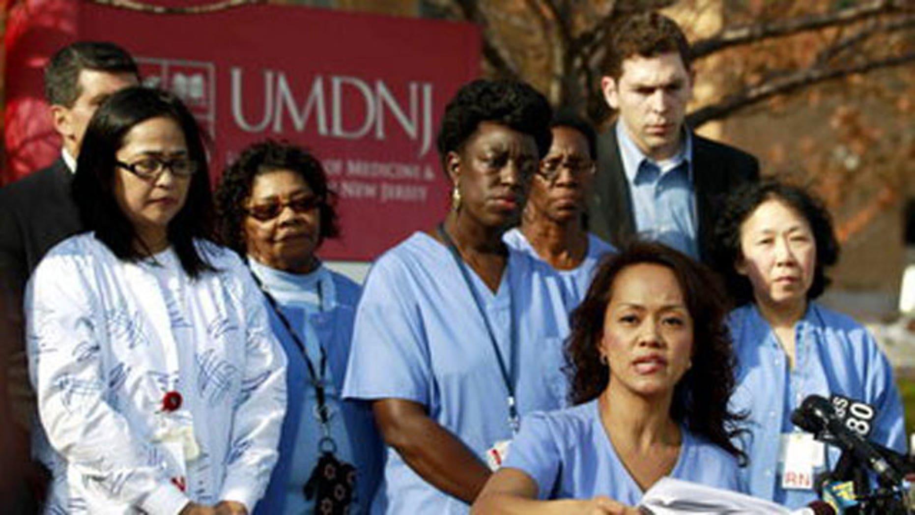November 14, 2011: Fe Esperanza Racpan Vinoya, bottom, a registered nurse at the University of Medicine and Dentistry of New Jersey, talks during a news conference in Newark, N.J.