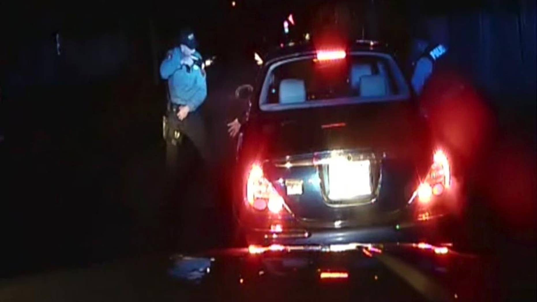 FILE - In this frame grab from an officer's dashboard camera taken Dec. 30, 2014, and provided by the Bridgeton, N..J. Police Department, police officers Braheme Days and Roger Worley stand near a car they pulled over for running a stop sign in Bridgeton. A grand jury has voted not to file charges against the two police officers for fatally shooting a man who defied orders by stepping out of a car with his hands raised during a traffic stop, a killing captured by their patrol car's dashboard camera, prosecutors said Thursday, Aug. 20, 2015. (AP Photo/Bridgeton Police Department, File)