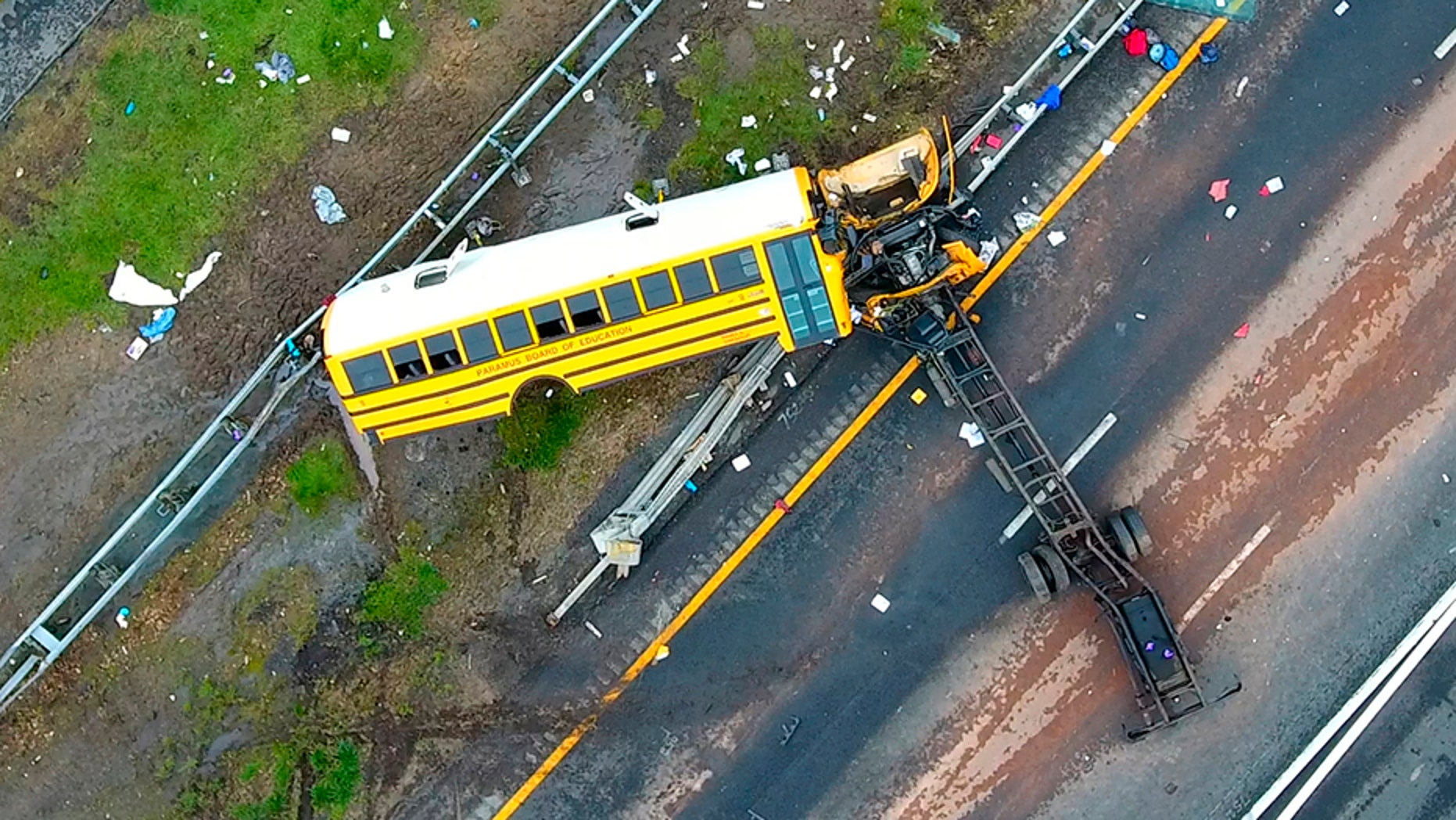 In this aerial photo, a school bus lies crashed on Route 80 in Mount Olive, N.J., Thursday, May 17, 2018. The Paramus school district says the bus was taking students on Thursday from East Brook Middle School to Waterloo Village, a historic site near the crash scene. The yellow school bus was carrying 38 students and seven adults when it crashed, killing a student and a teacher.