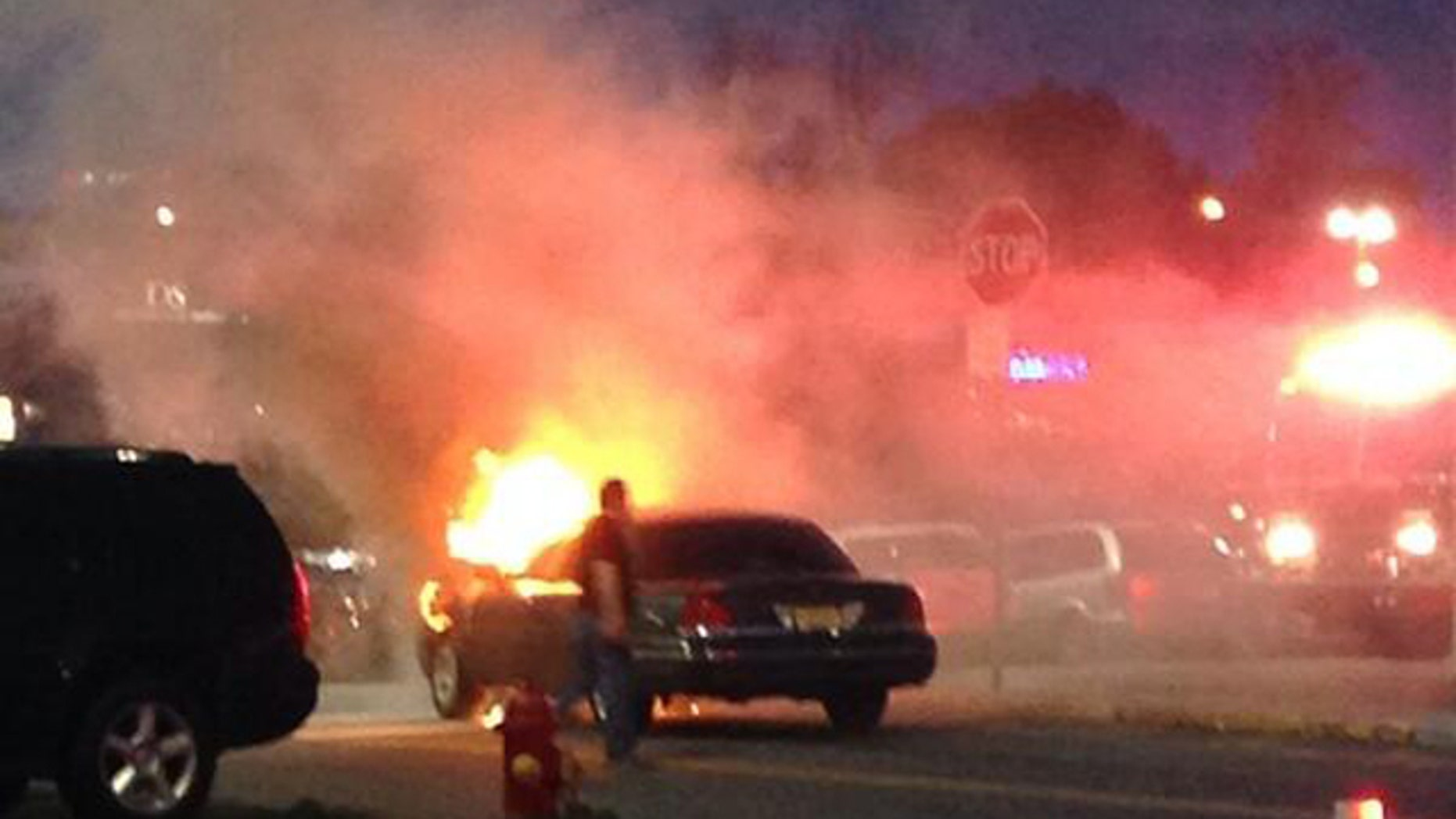 May 10, 2014: This photo provided by Brittany Berdy shows a car fire that authorities believe may have led to reports of gunshots that forced them to evacuate the Garden State Plaza mall in Paramus, N.J. New Jersey State Police Capt. Stephen Jones said that police have found no evidence that any shots were fired at the mall Saturday night. (AP Photo/Brittany Berdy)