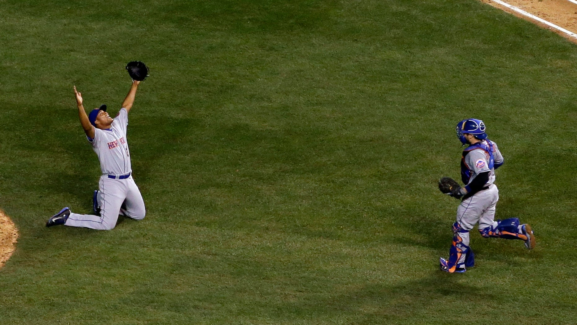 New York Mets pitcher Jeurys Familia, left, and catcher Travis d'Arnaud celebrates after Game 4 of the National League baseball championship series Wednesday, Oct. 21, 2015, in Chicago. The Mets won 8-3 to advance to the World Series. (AP Photo/David J. Phillip)