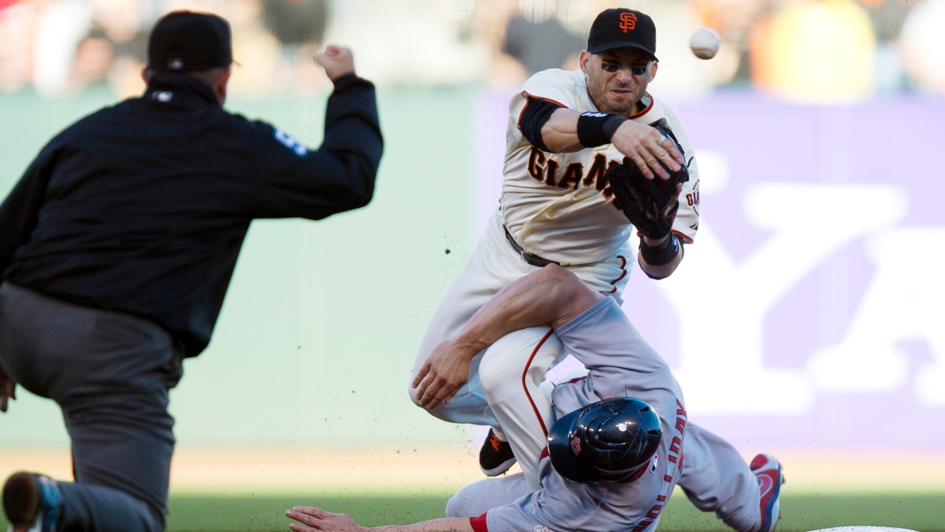 Oct. 15: San Francisco Giants second baseman Marco Scutaro (19) throws to first as he is taken out by St. Louis Cardinals' Matt Holliday (7) during Game 2 of NLCS.