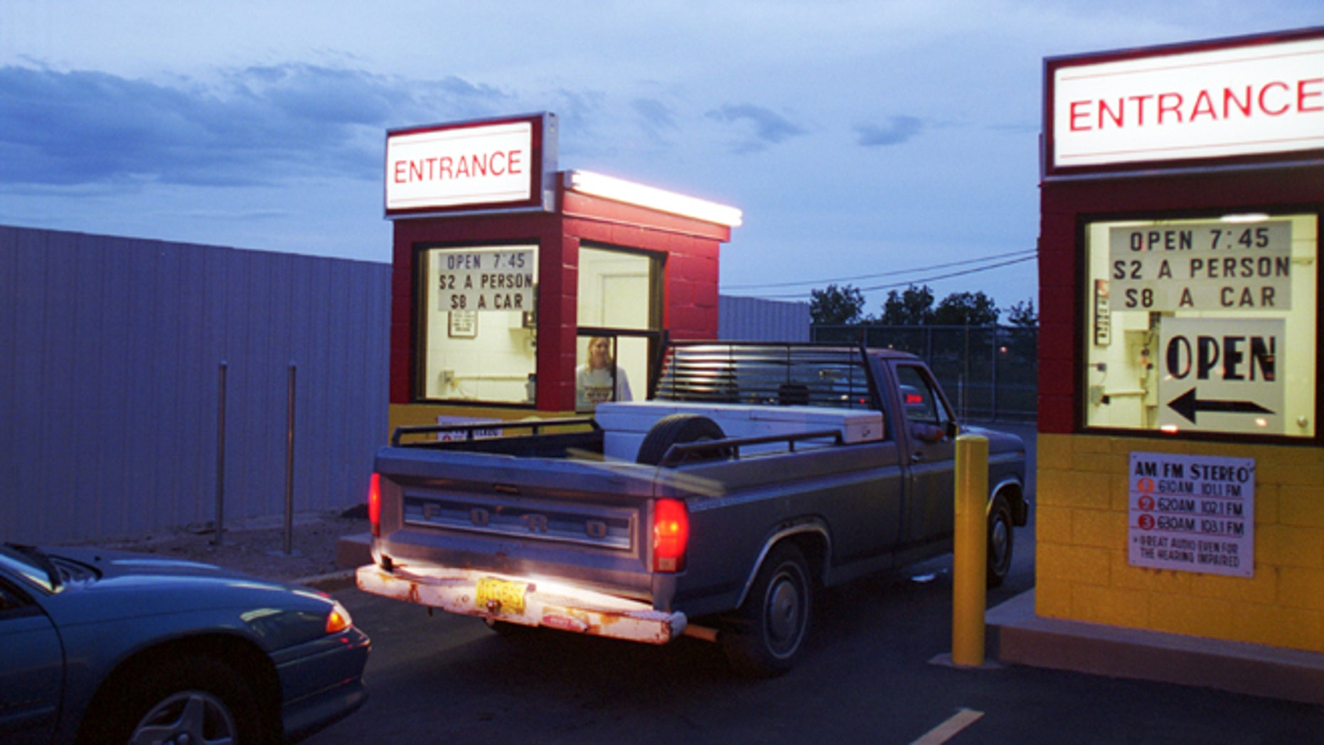 Cars and pickup trucks enter the Fiesta drive-in movie theater August 10, 2000 in Carlsbad, New Mexico. (Photo by Joe Raedle/Newsmakers)