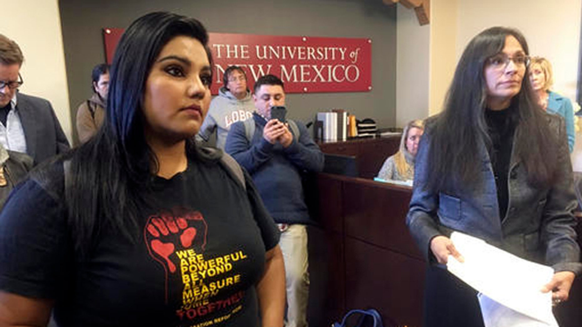 """University of New Mexico student LuzHilda Campos, left, and Chicano studies professor Irene Vasquez, right, present a letter with hundreds of signatures on Friday, Nov. 18, 2016, to school president Bob Frank asking him to declare the campus a """"sanctuary university,"""" in Albuquerque, N.M. A group of professors at the largest university in the nation's most Hispanic state are asking for more protection of immigrant students following the election of Republican Donald Trump. (AP Photo/Russell Contreras)"""