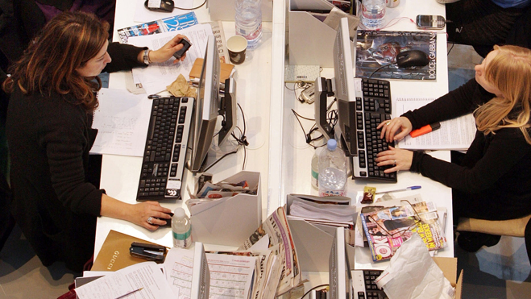 LONDON - NOVEMBER 03:  Production staff on the weekly fashion magazine, Grazia edit the magazine in a temporary office inside the Westfield shopping centre on November 3, 2008 in London. For one week Grazia magazine is being produced in the Westfield shopping centre and are offering shoppers free make-overs, fashion consultations and advice on pursuing a modeling career.   (Photo by Oli Scarff/Getty Images)