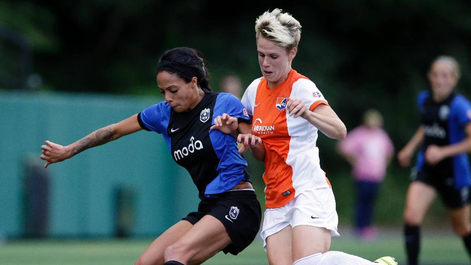 FILE - In this June 28, 2014, file photo, Seattle Reign's Sydney Leroux, left, and Sky Blue's Sophie Schmidt vie for the ball in the first half of an NWSL soccer game in Seattle. In the space of about a week, a group of players from the U.S. team wrapped up the regular season with their National Women's Soccer League teams, got together for an international friendly against Switzerland, and now face off in the NWSL playoffs. The country's top players are maintaining a delicate balance between supporting the NWSL at home while gearing up for a busy two years that include the women's World Cup in Canada next summer and then 2016 Rio Olympics. (AP Photo/Elaine Thompson, File)