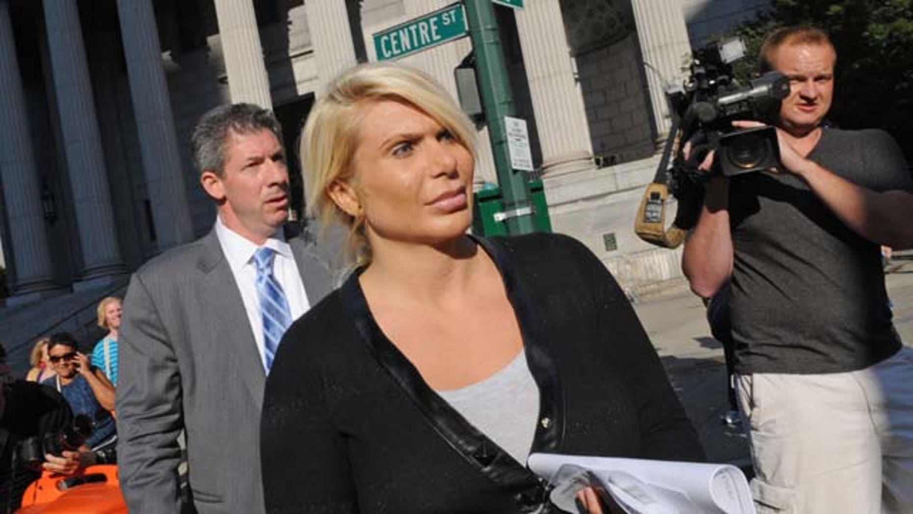 August 6, 2013: Kristin Davis, center, leaves Manhattan federal court with her attorney Daniel Hochheiser, left, in New York. Davis, a former madam running against former Gov. Eliot Spitzer in the race for New York City comptroller, peddled hundreds of powerful painkillers and other prescription pills in exchange for Ecstasy and cash from a drug dealer wearing a wire, federal authorities said Tuesday. (AP Photo)
