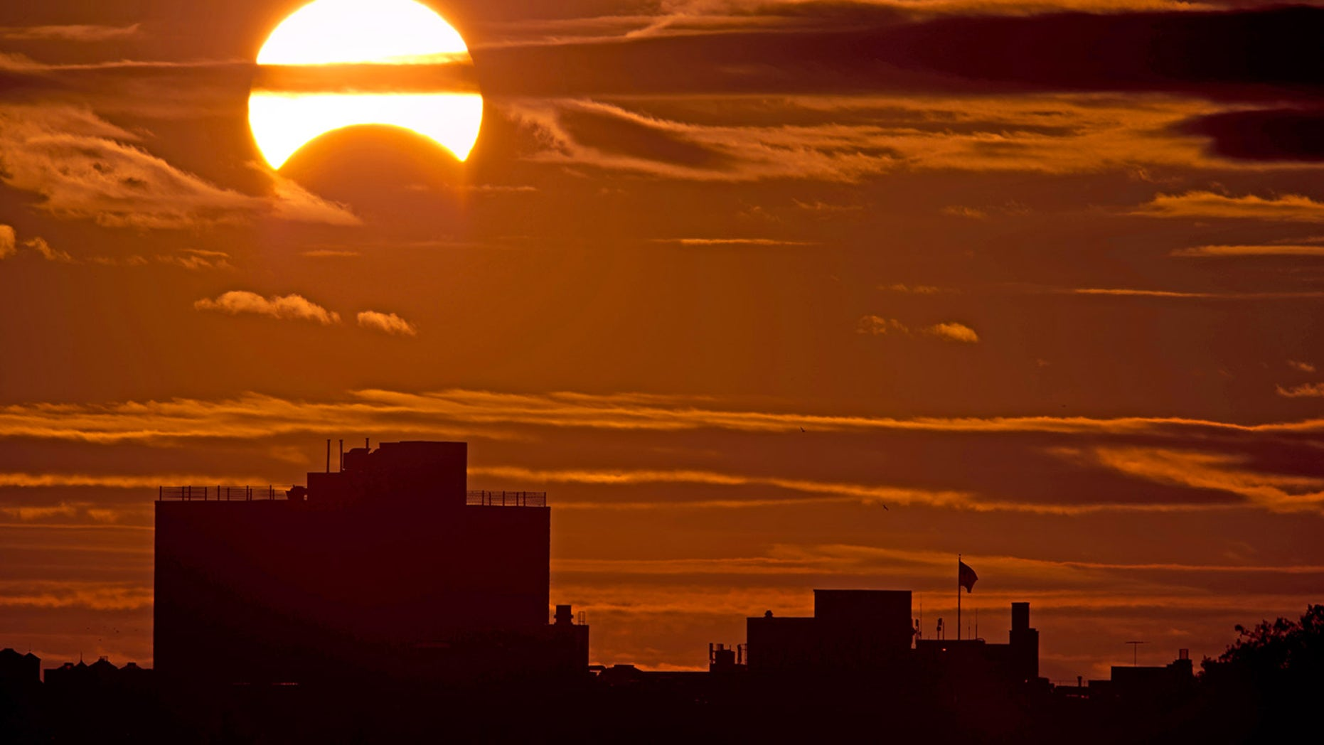 A partial solar eclipse is seen just after sunrise over the Queens borough of New York across the East River on Nov. 3, 2013.