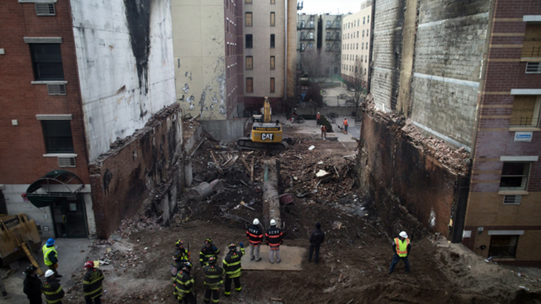 Workers stand beside the recently cleared basement of the two buildings leveled by an explosion on Wednesday in the East Harlem neighborhood of New York, Sunday, March 16, 2014. A pair of congregations gathered to mourn Sunday, one for its lost church and one for two members who lost their lives in the massive explosion. (AP Photo/John Minchillo)