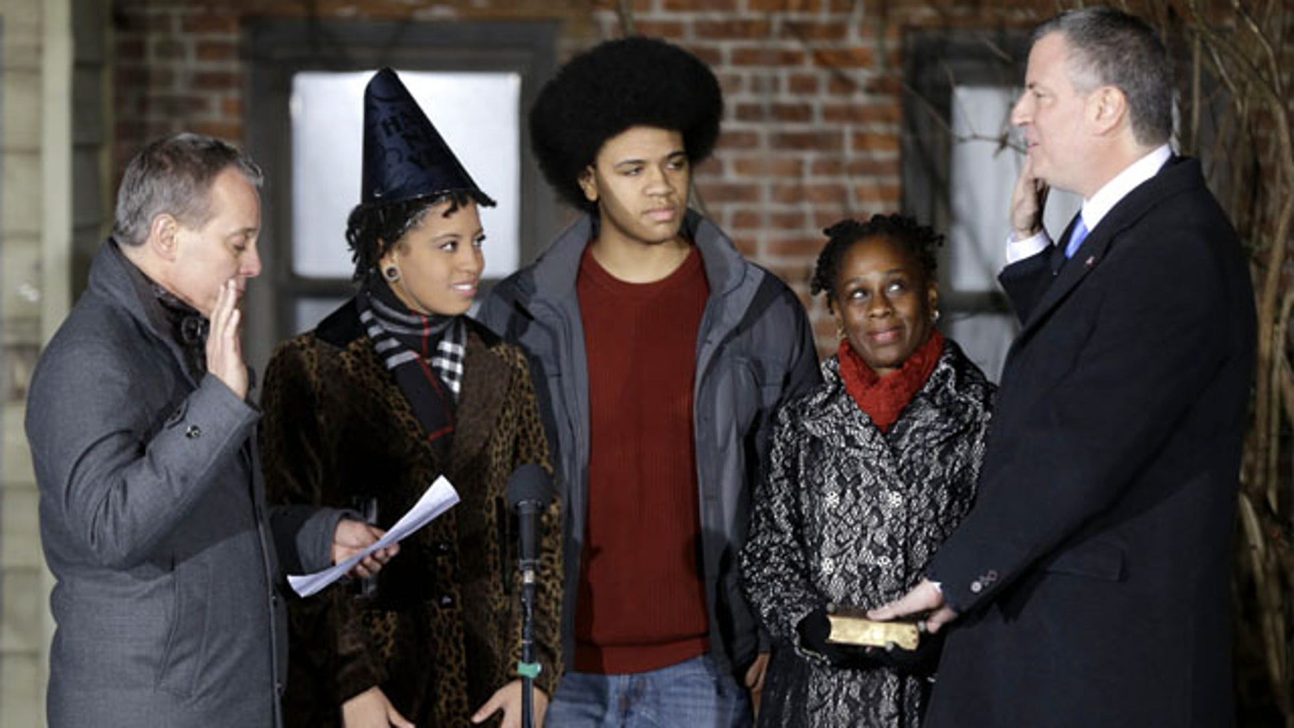 January 1, 2013: Bill de Blasio, right, is sworn in as the mayor of New York City by State Attorney General Eric Schneiderman, left, while his family, Chiara de Blasio, second from left, Dante de Blasio, center, and Chirlane McCray look on. De Blasio took the oath of office moments after midnight at his home in Park Slope, Brooklyn. (AP Photo)