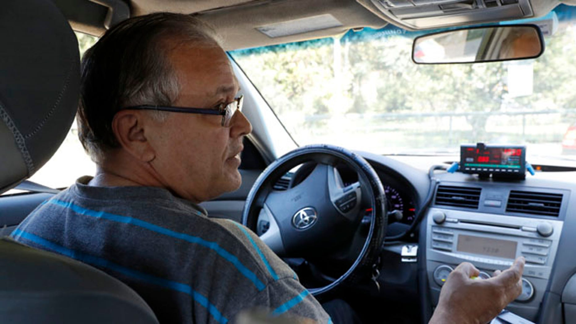 In this Wednesday, Aug. 24, 2016 photo, taxi driver Luis Rosado speaks to an Associated Press reporter while stopped at a red light in New York. Nearly 96 percent of cabbies are immigrants, and the city has dropped a longstanding requirement that they be required to speak and understand basic English. While immigrant advocates say the change makes it easier for newcomers to get work behind the wheel, some customers say it could make riding in a cab even more of an adventure. (AP Photo/Mary Altaffer)