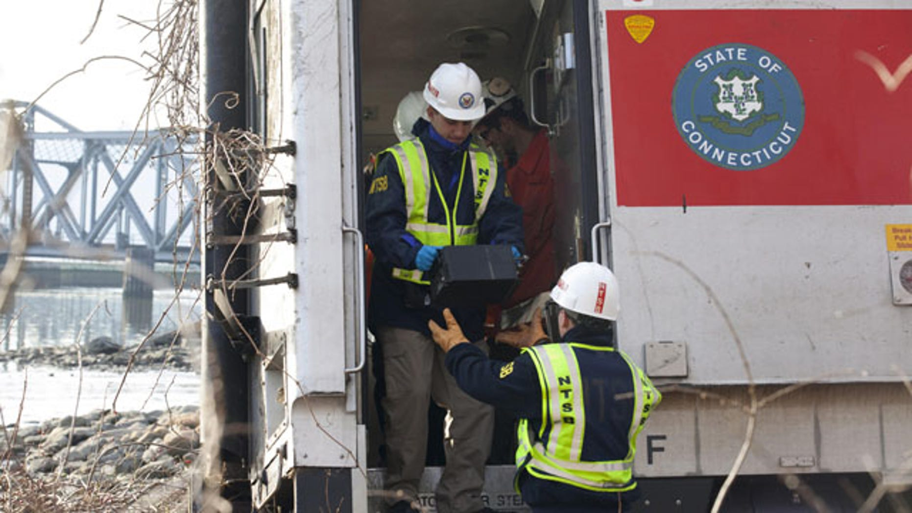 December 1, 2013: NTSB investigator George Haralampopoulous hands a data recorder down to Mike Hiller from the derailed Metro-North train in the Bronx borough of New York. (AP Photo/NTSB)