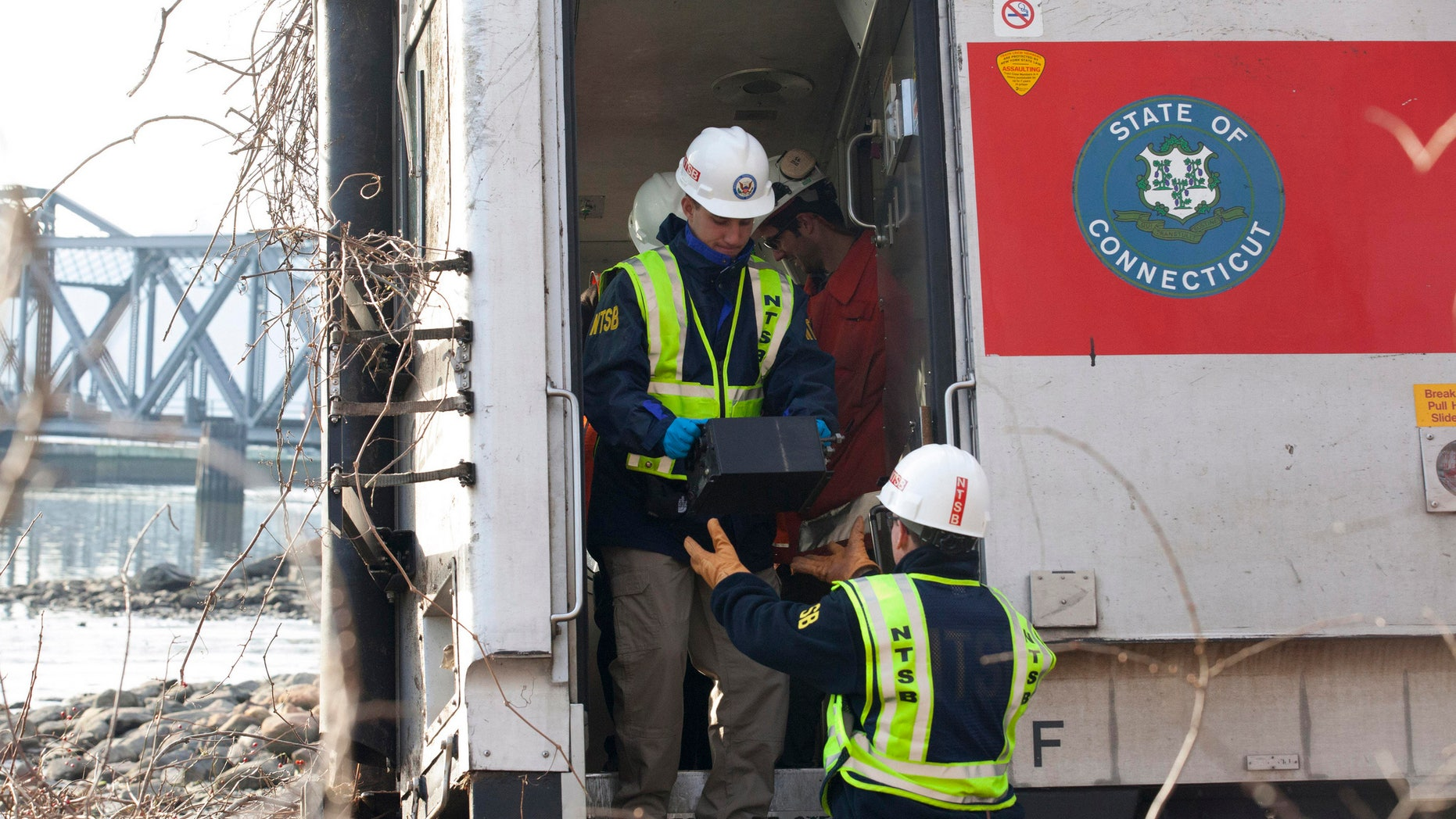 NTSB investigator George Haralampopoulous hands a data recorder down to Mike Hiller from the derailed Metro-North train in the Bronx borough of New York, on Dec 1, 2013.