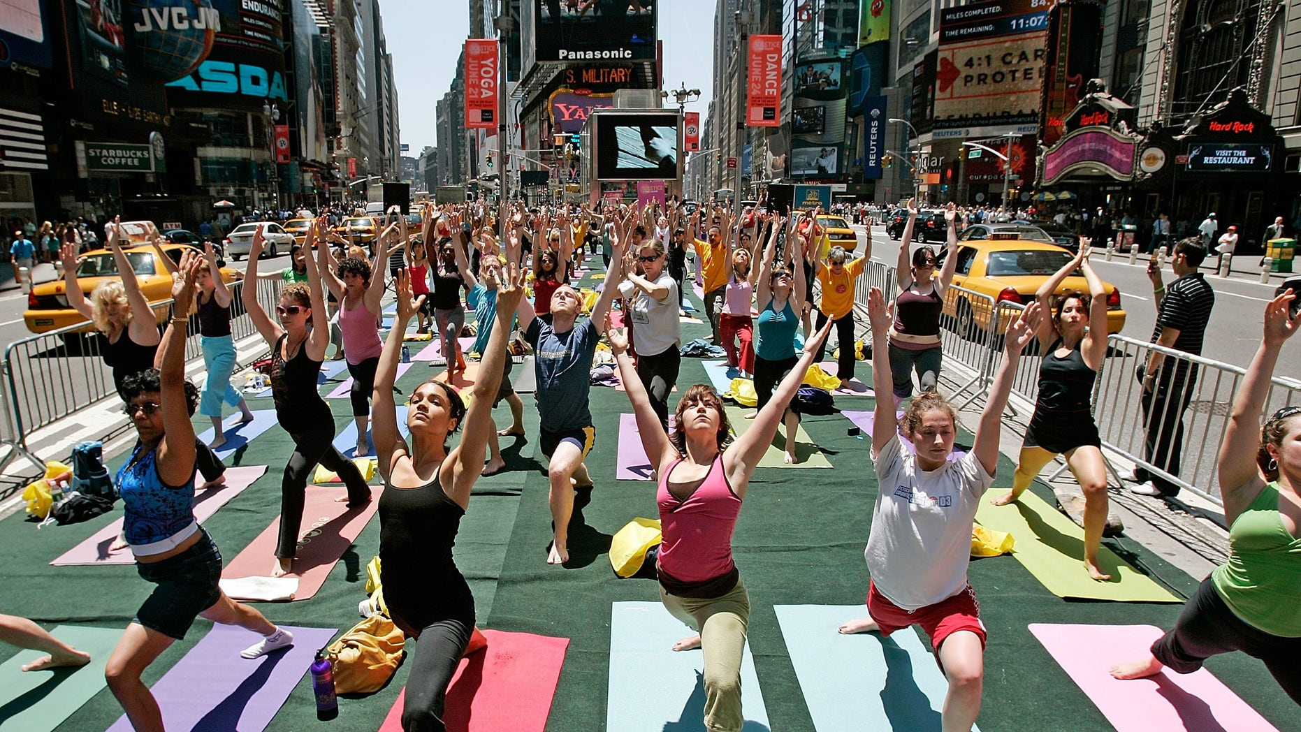 Yoga enthusiasts from across the country unite in Times Square as taxis drive past in New York City.