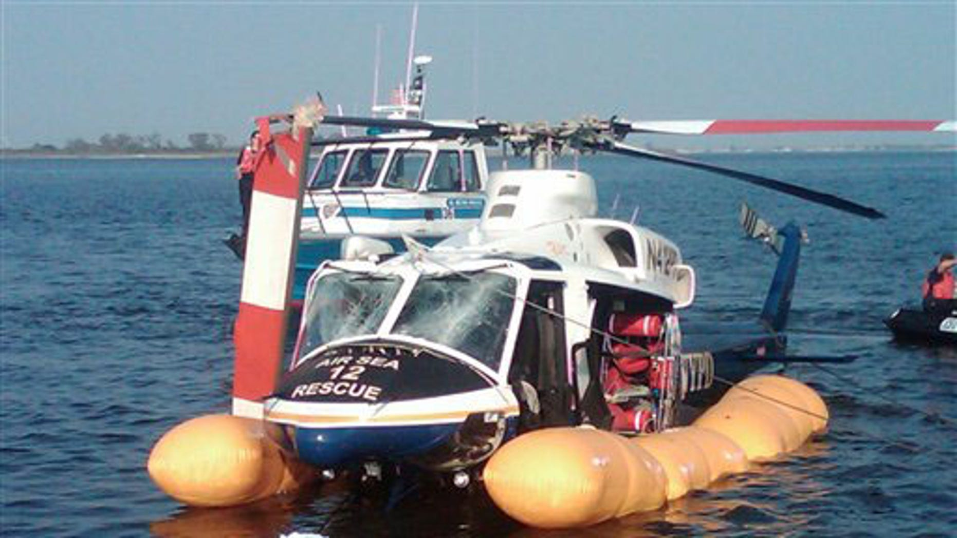 In this photo released by the New York City Police Department, a damaged NYPD helicopter is towed off Jamaica Bay after making an emergency landing, Wednesday, Sept. 22, 2010, in New York. The helicopter sustained a broken rotor and damaged windshield but the three-member flight crew, a trainee and two scuba divers escaped serious harm. One person was treated for a minor injury.