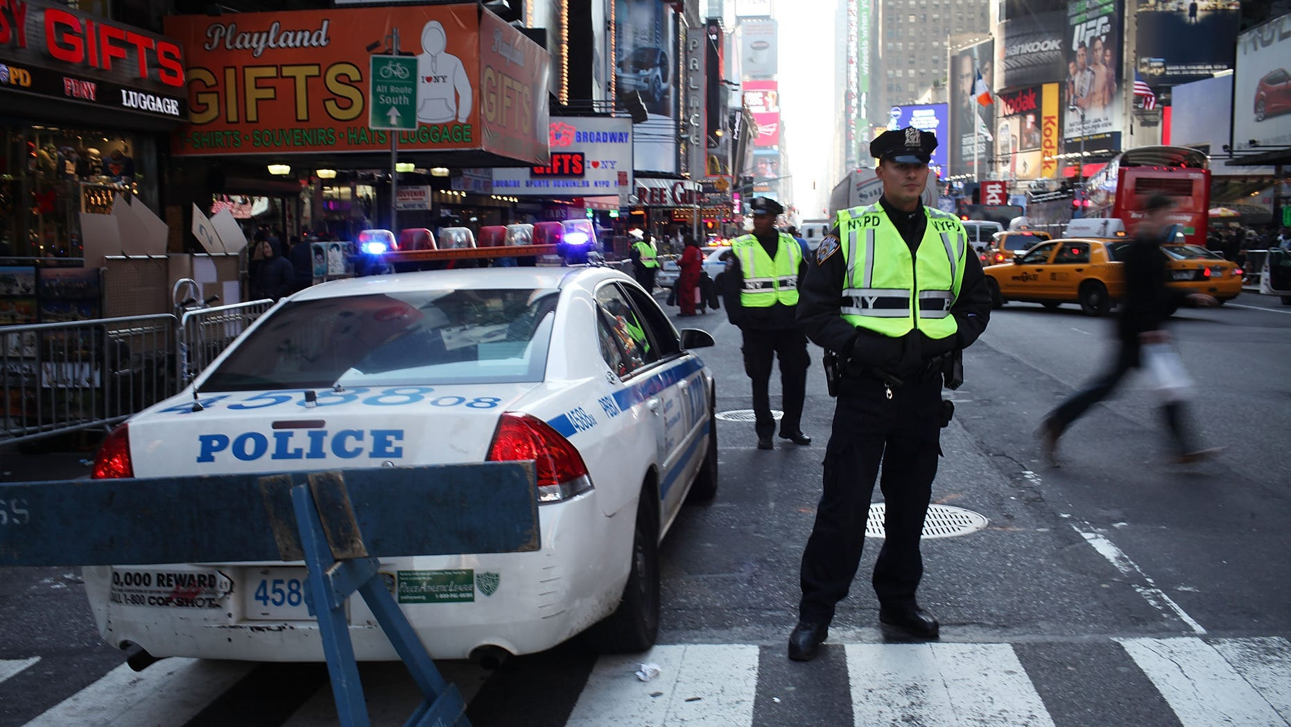 NEW YORK, NY - DECEMBER 30: Police stand guard as thousands of people crowd into Times Square on the day before New Years Eve on December 30, 2011 in New York City. Tens of thousands of tourists and New Yorkers will crowd into Times Square on New Year's Eve to ring in 2012 and watch the historic ball drop.  (Photo by Spencer Platt/Getty Images)
