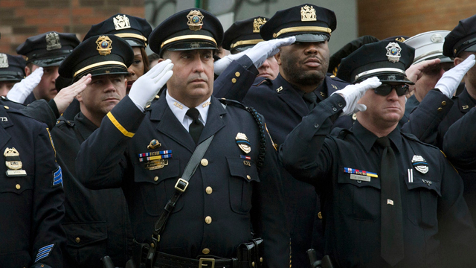 Jan. 4, 2015: Police officers salute along the procession route during the funeral of New York Police Department Officer Wenjian Liu, in the Brooklyn borough of New York. (AP Photo/John Minchillo)