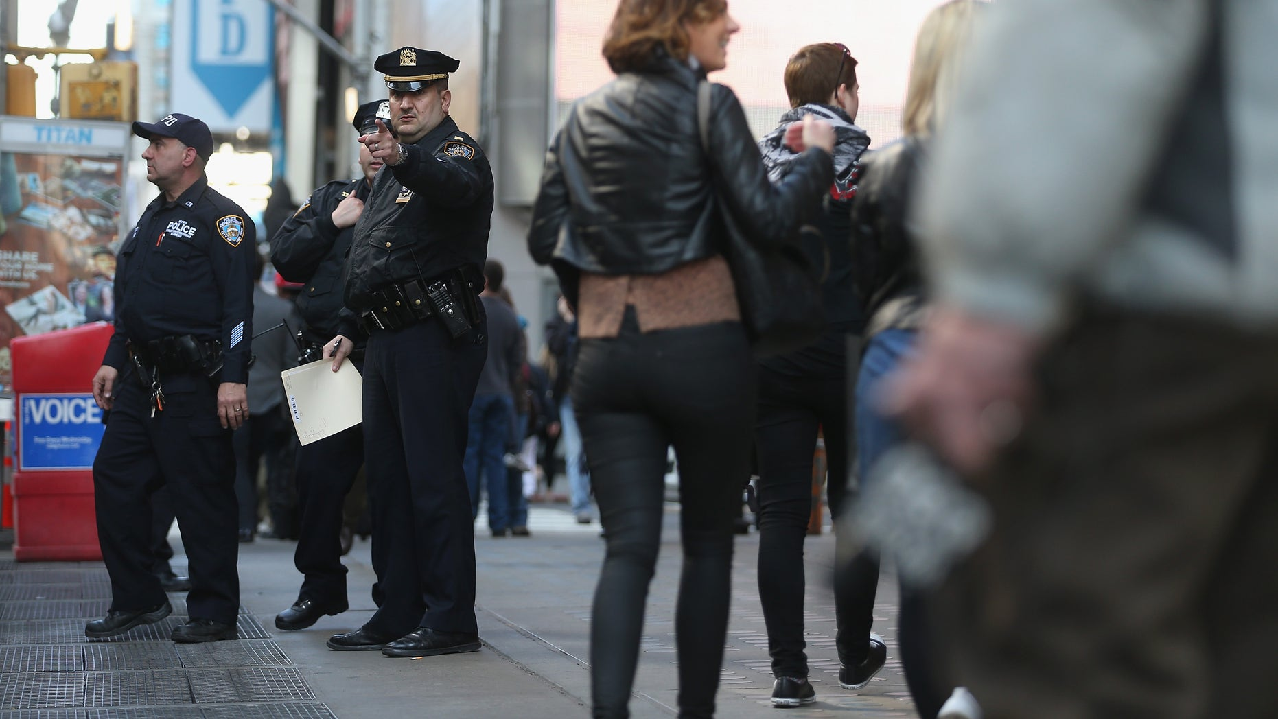 NEW YORK, NY - APRIL 15:  New York Police Department officers gather at the edge of Times Square in Manhattan on April 15, 2013 in New York City. The city has announced it will implement heightened security measures in response to today's bombings at the Boston Marathon.  (Photo by Mario Tama/Getty Images)