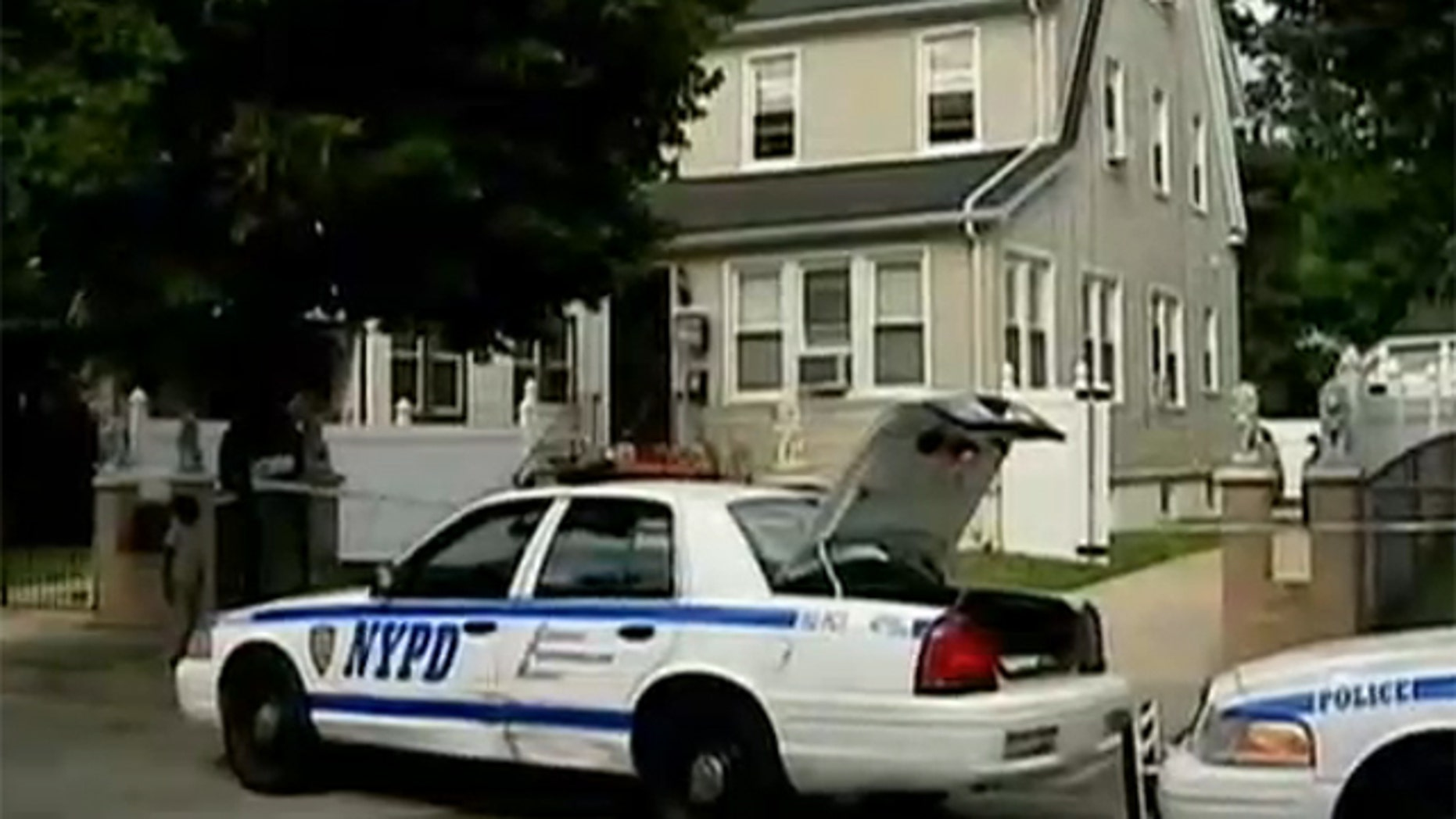 July 27, 2012: Detectives sit outside a home.