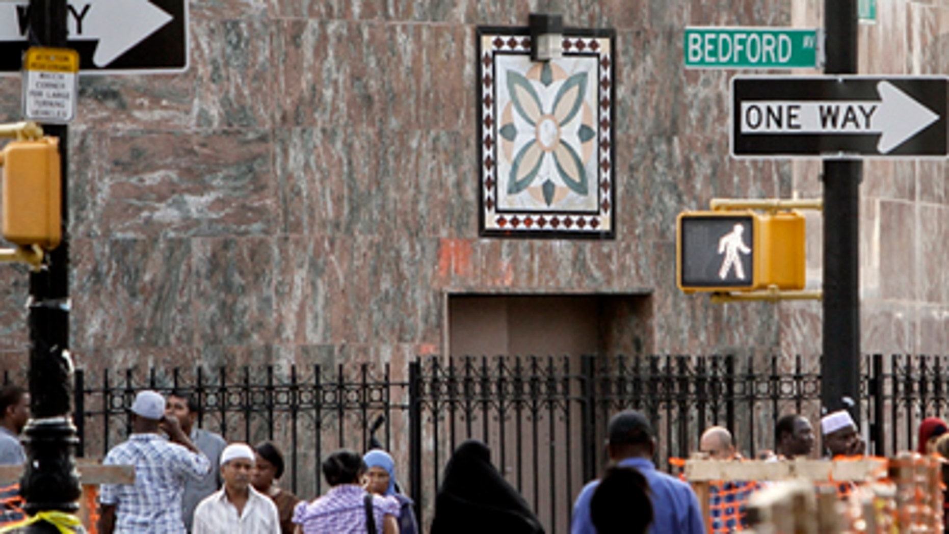 In this Aug. 18, 2011 photo, people pass below a New York Police Department security camera, upper left, which is above a mosque on Fulton St., in the Brooklyn neighborhood of Bedford-Stuyvesant in New York.