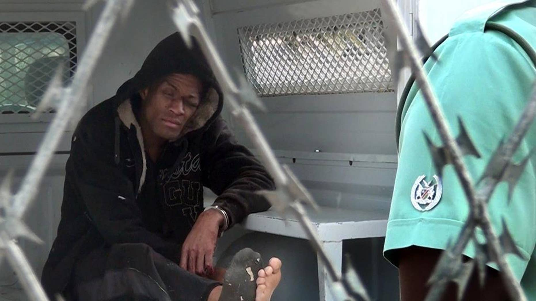 American citizen Marcus Kevin Tomas, sits inside a police van in Windhoek, Namibia, Monday, Nov. 3, 2014. Tomas, on Sunday climbed a tree inside the Windhoek Central Prison and tried to jump over the barbed wire fence but instead landed on top of the fence. Prison authorities told the press agency that they found Tomas hanging from the barbed fence and called emergency medical services to remove him. (AP Photo/George Hendriks)