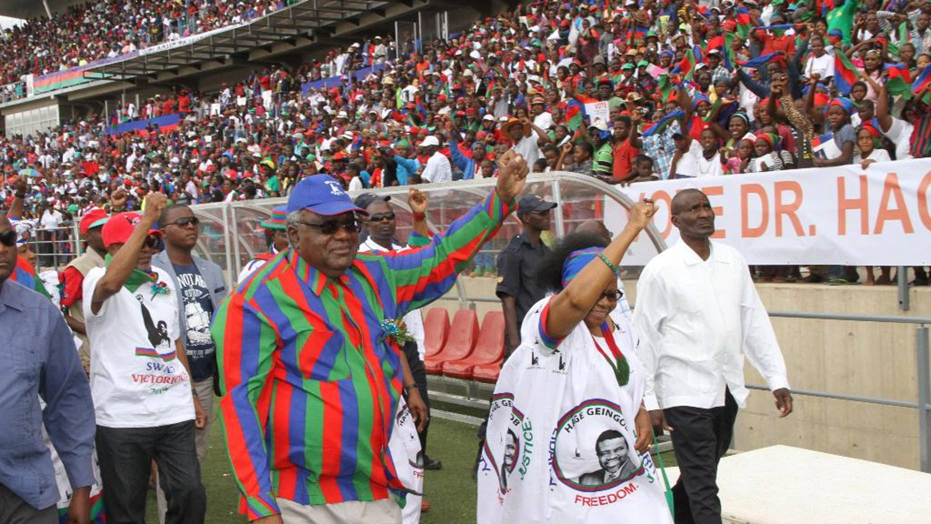 In this photo taken Saturday, Nov. 22, 2014, Namibian president Hifikepunye Pohamba, centre left, and his first lady, Penehupifo Pohamba, centre right, arrive at the Sam Nujoma Stadium in Windhoek, Namibia for an election rally.  Namibians go to the polls Nov. 28 to elect a new president and national assembly. (AP Photo/Joseph Nekaya, Namibian Press Association)