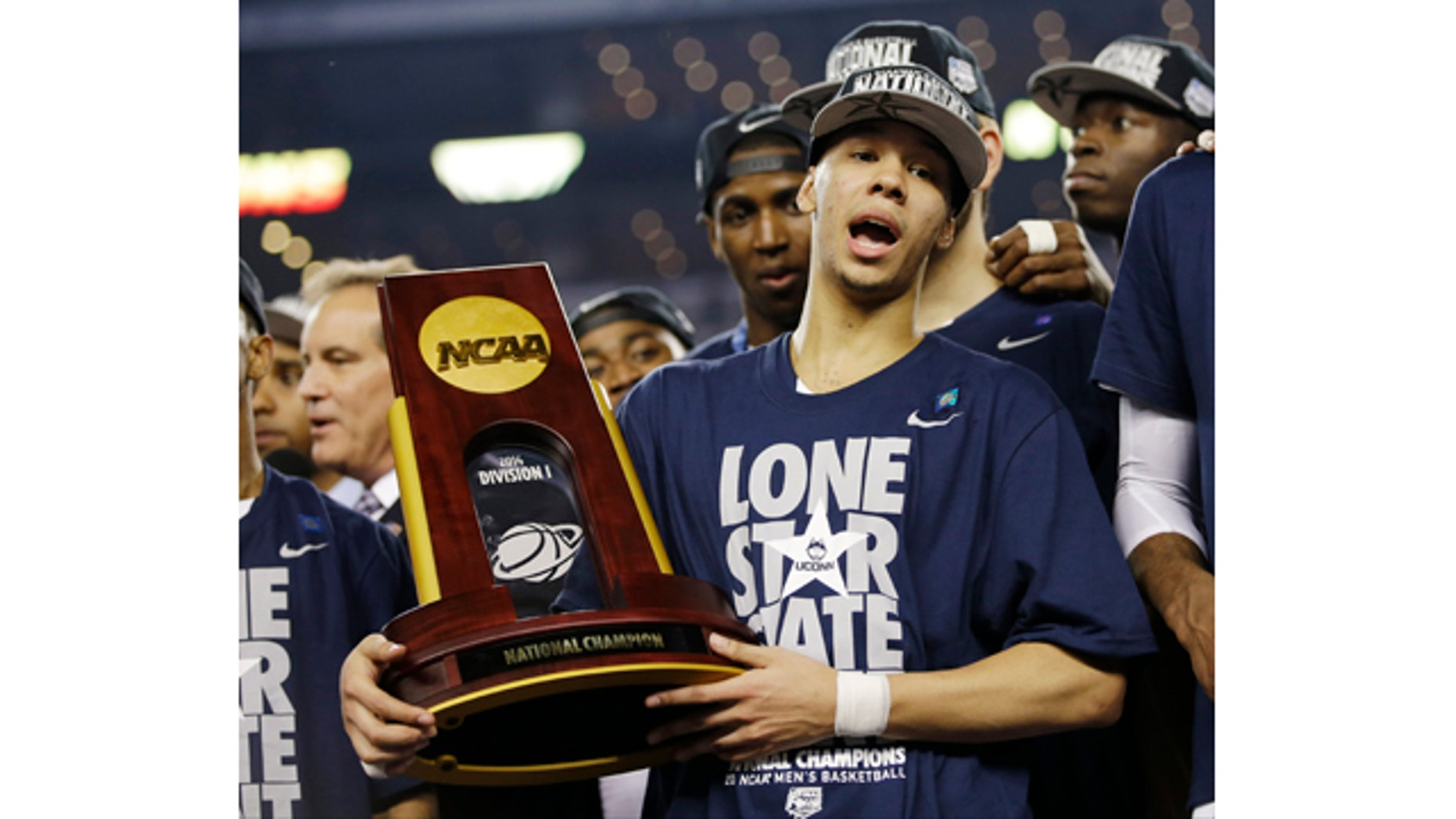 April 7, 2014: Connecticut guard Shabazz Napier holds the championship trophy after defeating Kentucky 60-54, at the NCAA Final Four tournament college basketball championship game in Arlington, Texas. (AP Photo/David J. Phillip)