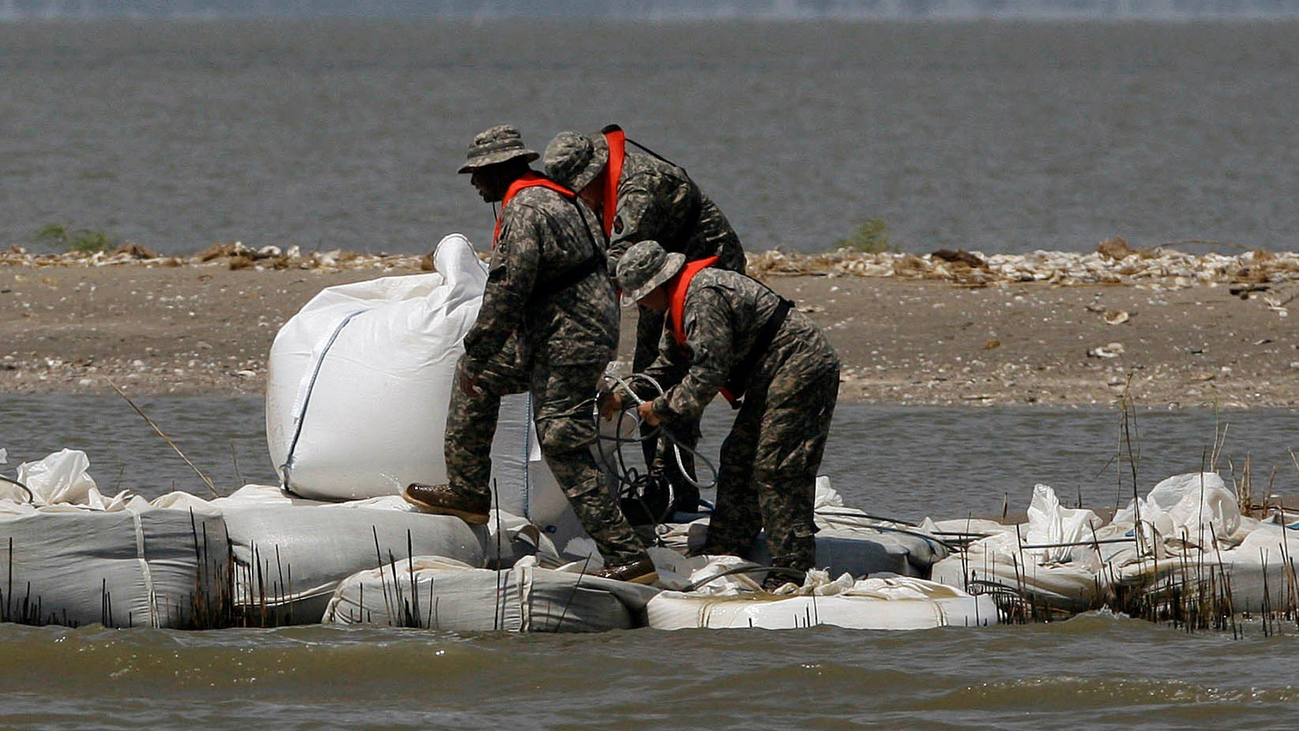National Guardsmen walk along a barrier created by the National Guard from 2,000 pound bags of sand to block a pass in a effort to protect Scofield bay from oil from the Deepwater Horizon spill, Friday, June 11, 2010, near Venice, La.. (AP Photo/Eric Gay)