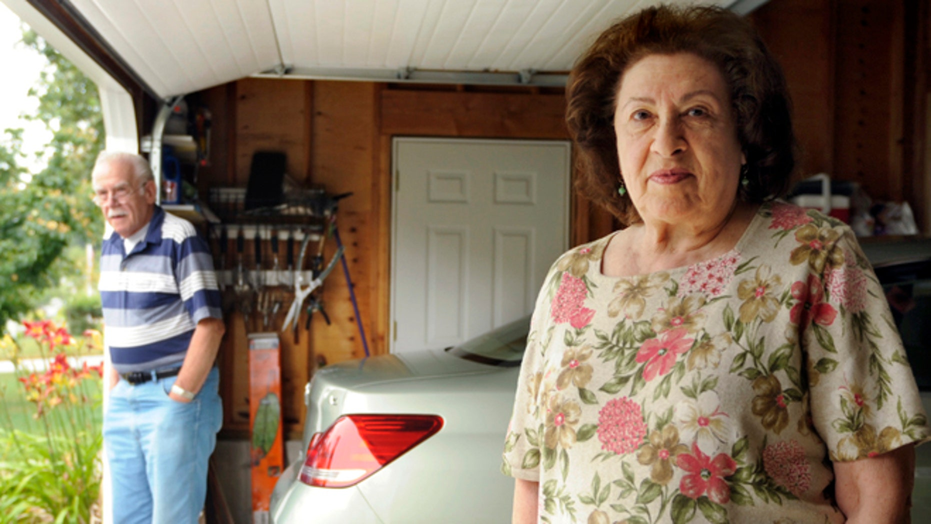 In this July 20, 2012 photo, Al, left, and Sondra Tuchman stand in the garage of their Montville, Conn., home. Sondra Tuchman said her garage-door opener was no longer opening and closing the door, and a representative of the door company told her they had received similar complaints from customers in nearby towns. The U.S. Navy said Monday, July 23, 2012, that a new radio system at the Naval Submarine Base in Groton may be interfering with the garage-door openers. (AP Photo/Sean D. Elliot, The Day)  MANDATORY CREDIT: SEAN D. ELLIOT/THE DAY