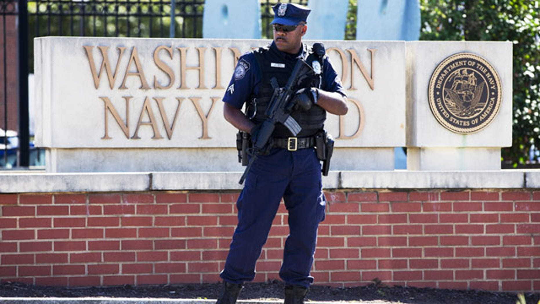 September 17, 2013: An armed officer who said he is with the Defense Department, standing near guard the gate at the Washington Navy Yard the day after a gunman launched an attack inside the Yard. An independent review triggered by the Washington Navy Yard killings last year says threats to Defense Department personnel and facilities increasingly are coming from within. It says the department must rethink its outdated security theory that suggests defending the perimeters can keep threats away. Instead, it says that terrorism, espionage and even physical threats are coming from trusted insiders. (AP Photo/Jacquelyn Martin, File)
