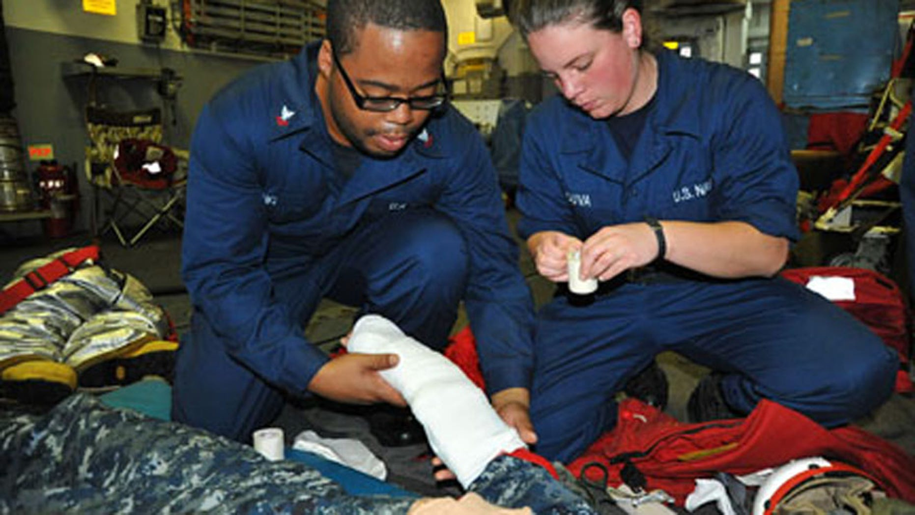 Yeoman 2nd Class Warren Ewing and Sonar Technician (Surface) Seaman Kelly Souva, both assigned to the Arleigh Burke-class guided-missile destroyer USS McCampbell (DDG 85), respond to a simulated medical casualty during a general quarters drill at sea.