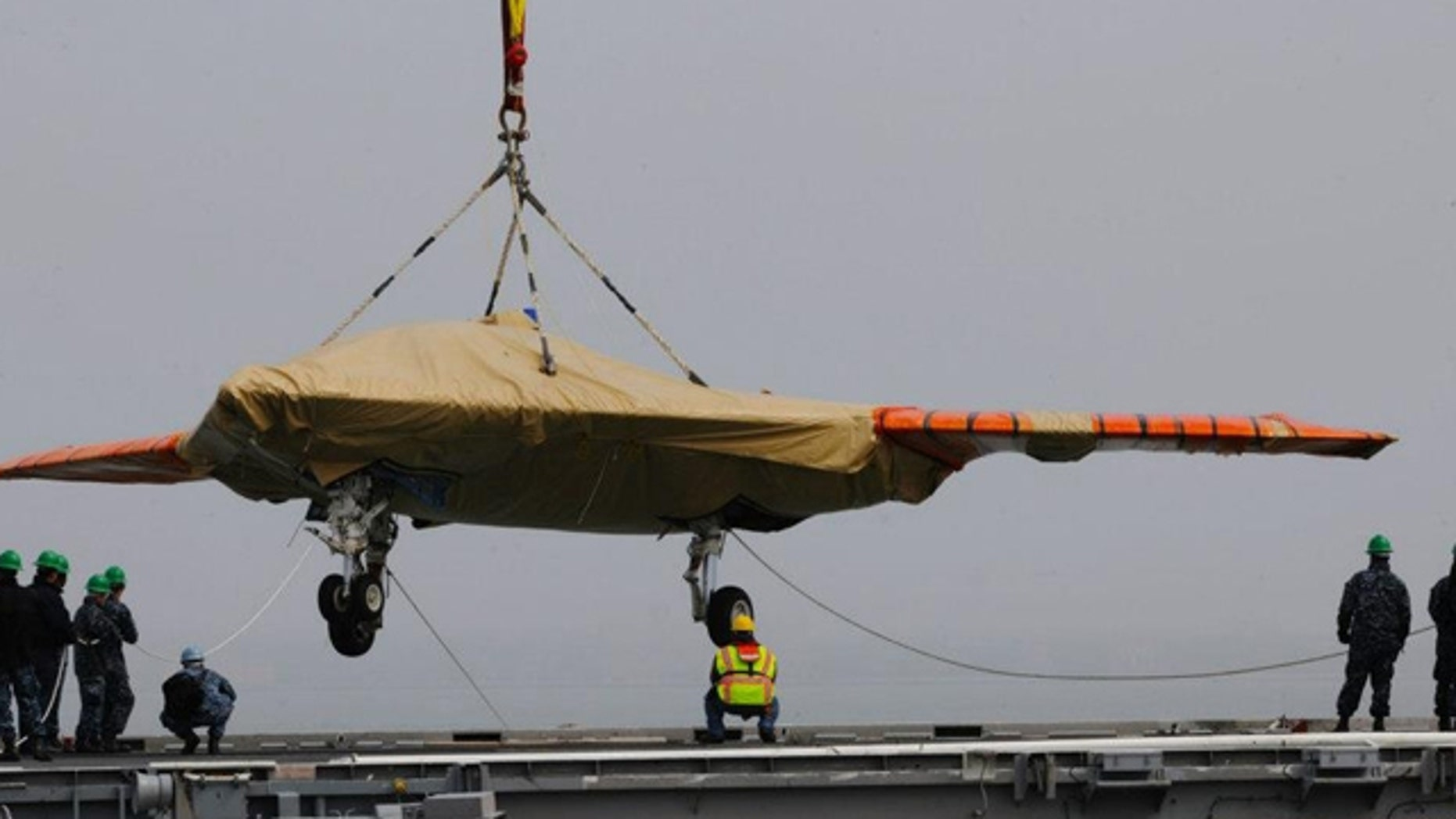 May 6, 2013: A X-47B Unmanned Combat Air System demonstrator is loaded onto the flight deck of the aircraft carrier USS George H.W. Bush.