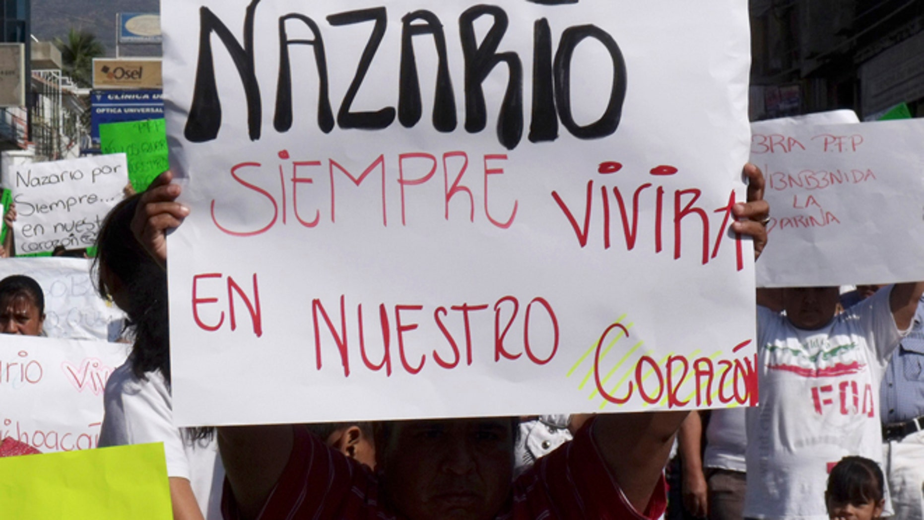 """FILE - In this Dec. 12, 2010 file photo, a man holds a sign that reads in Spanish """"Nazario will always live in our hearts,"""" referring to La Familia drug cartel leader Nazario Moreno Gonzalez during a demonstration after the government announced he was killed in Apatzingan, Mexico. Years later on Sunday, March 9, 2014, officials say they are trying to determine if a man killed in an early morning shootout is Moreno. Some residents of Michoacan have reported seeing Moreno as his former cartel, La Familia Michoacana, was morphing into the more vicious and powerful Knights Templar. (AP Photo/Primera Plana, File)"""