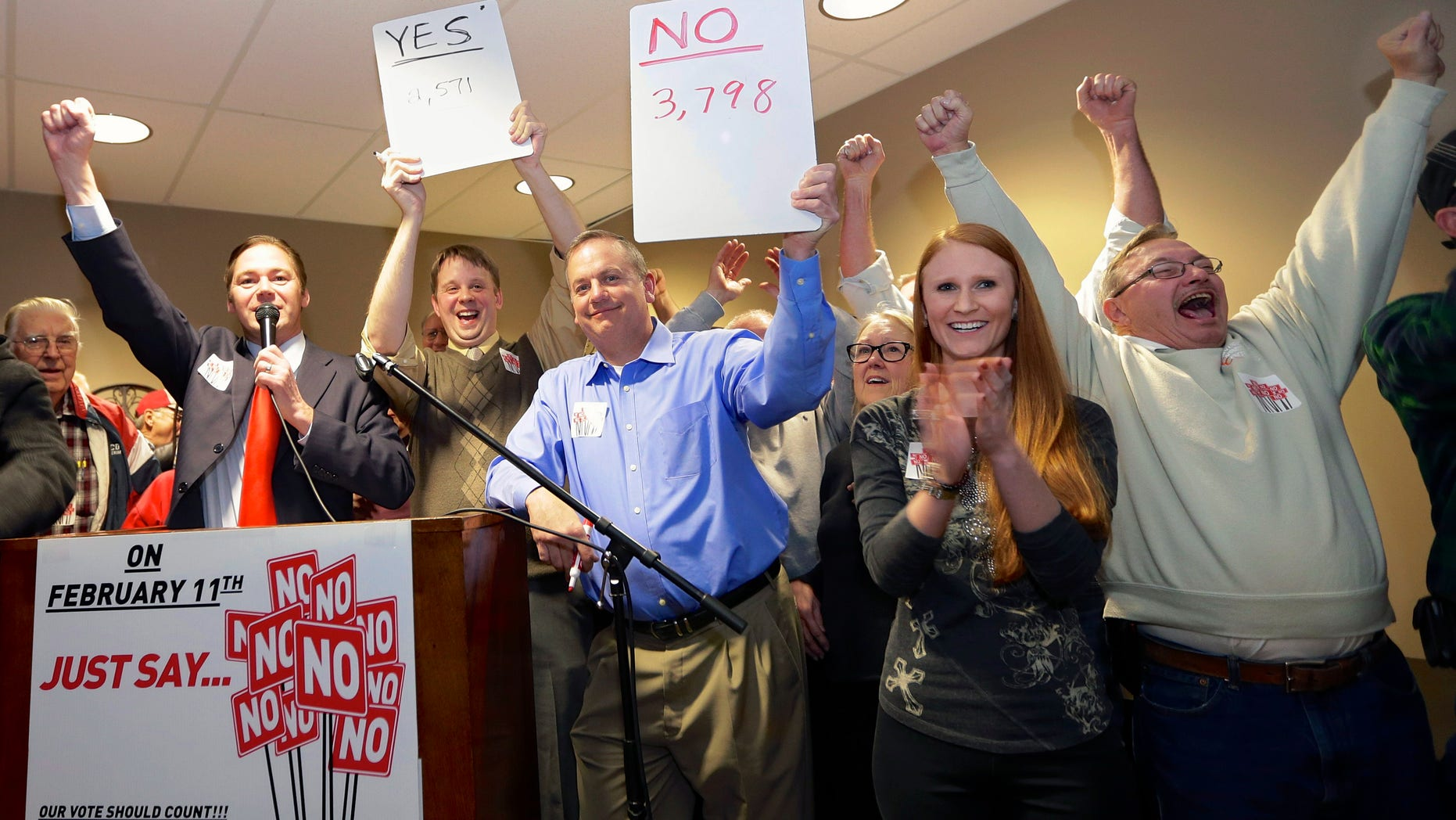 State Sen. Charlie Jansssen of Fremont, second left, Jeremy Jensen, third left, and John Wiegert, center, celebrate with other activists in Fremont, Neb., Tuesday, Feb. 11, 2014, after city voters have decided by voting no, to uphold the law designed to bar immigrants from renting homes if they dont have legal permission to be in the U.S. (AP Photo/Nati Harnik)