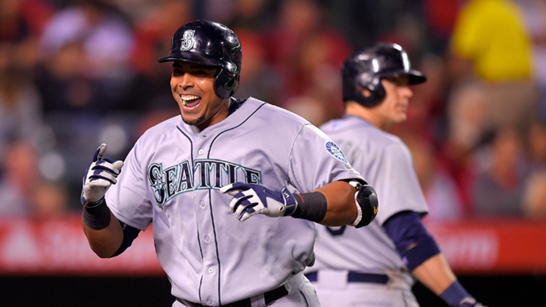 Seattle Mariners' Nelson Cruz, left, celebrates after hitting a solo home run against the Los Angeles Angels as Logan Morrison walks up to bat during the seventh inning of a baseball game, Monday, May 4, 2015, in Anaheim, Calif. Morrison also hit a solo home run in the inning. (AP Photo/Mark J. Terrill)