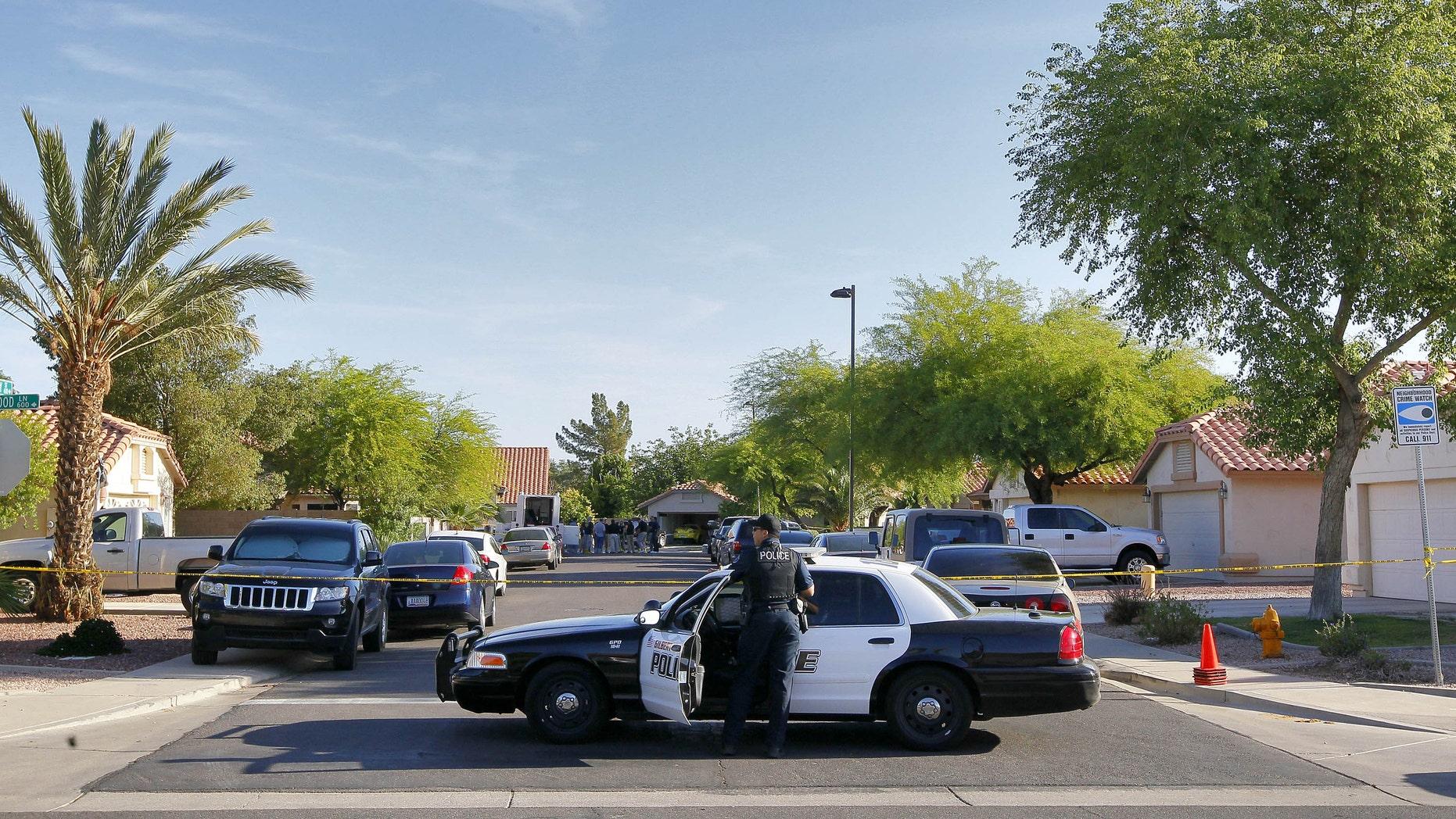 A Gilbert police officer blocks the street outside a shooting crime scene Thursday, May 3, 2012 in Gilbert, Ariz. (AP Photo/Matt York)
