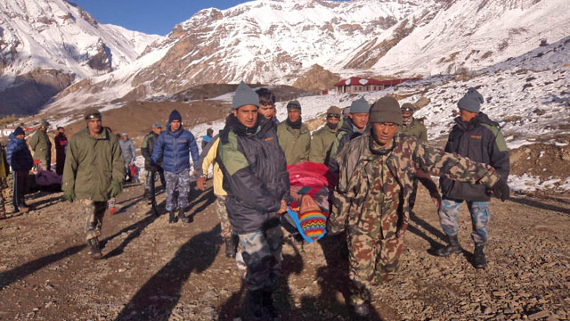 October 15, 2014: In this photo provided by the Nepalese army, soldiers carry an avalanche victim before he is airlifted in Thorong La pass area. (AP Photo/Nepalese Army)