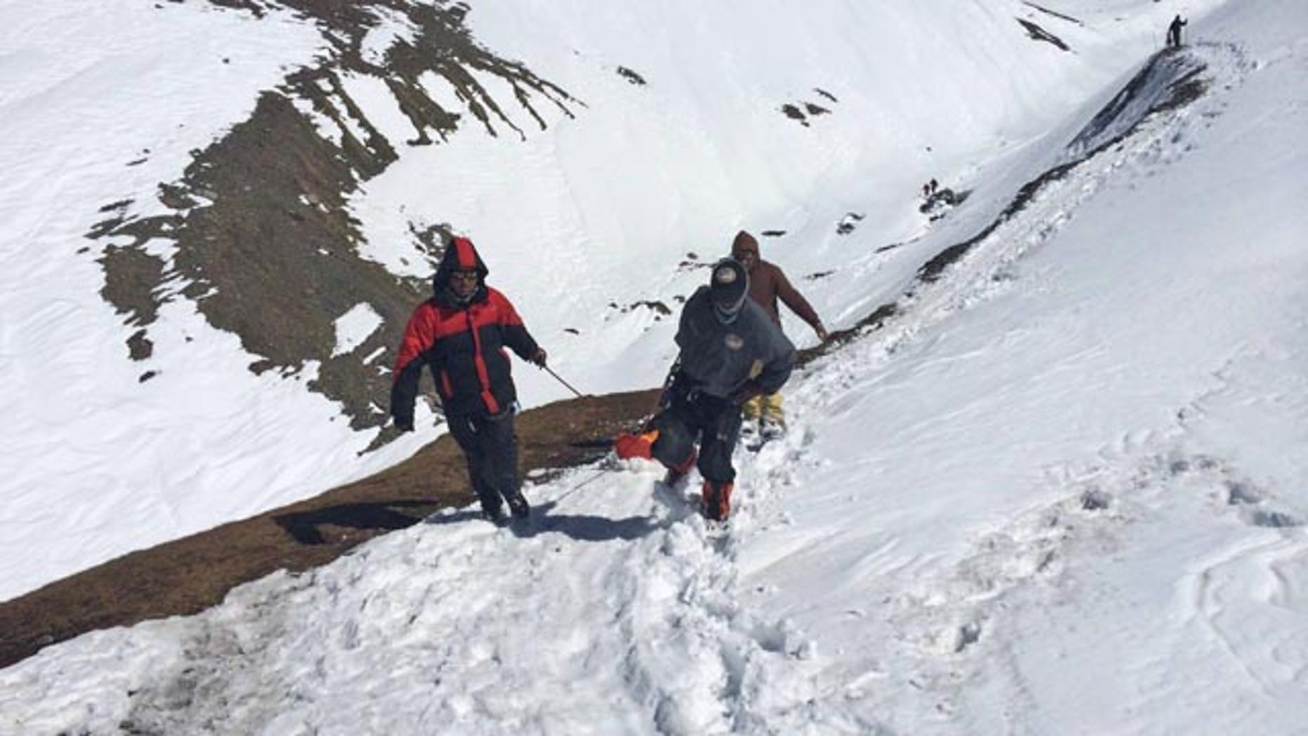 October 17, 2014: In this handout photo provided by the Nepalese army, rescue team members carry the body of an avalanche victim at Thorong La pass area. (AP Photo/Nepalese Army)